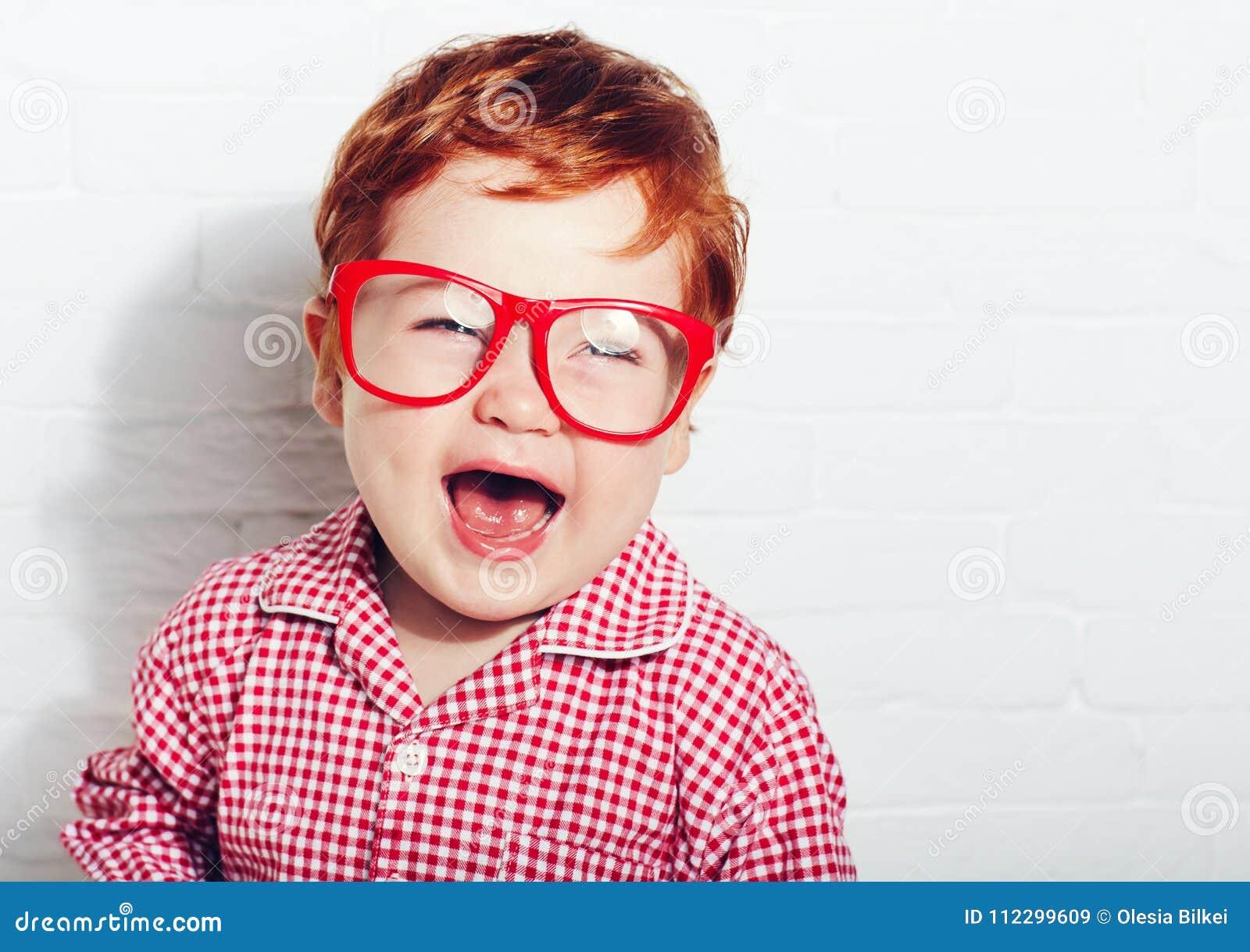 Retrato del niño pequeño de risa lindo en vidrios