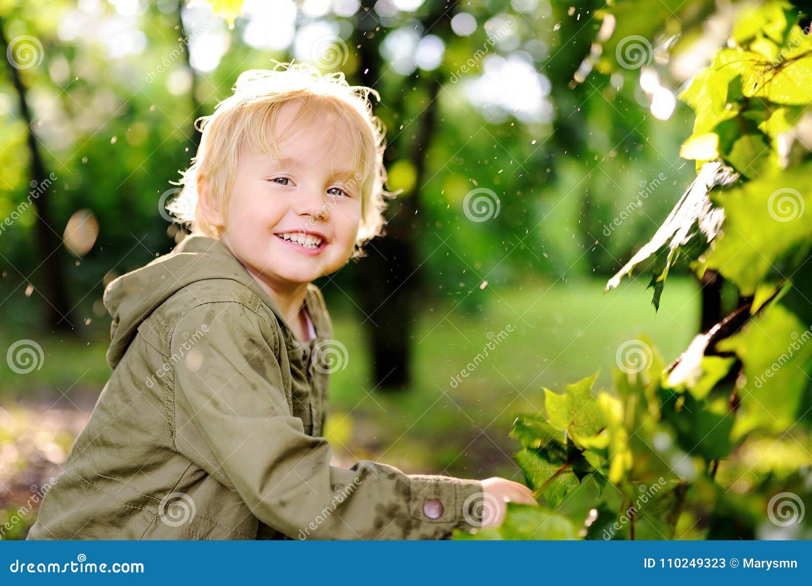Retrato del niño pequeño feliz lindo que se divierte en parque del verano después de lluvia