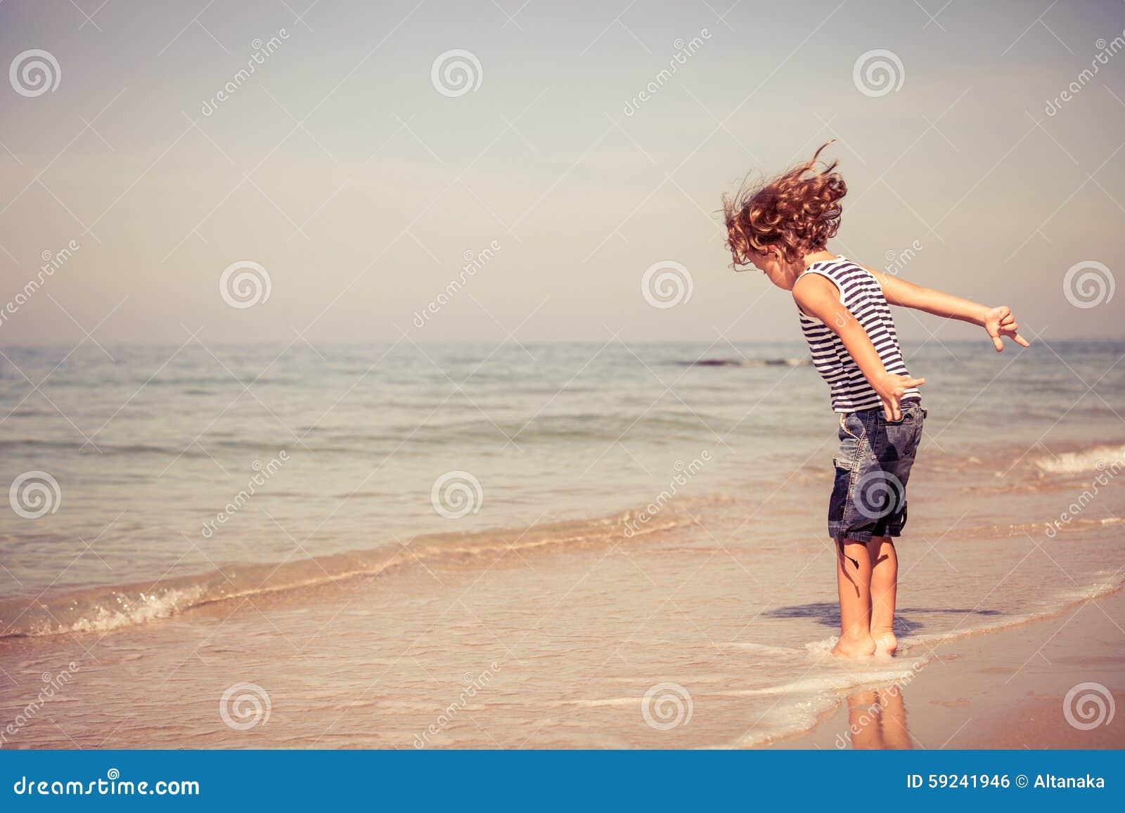 Download Retrato Del Niño Pequeño Que Se Coloca En La Playa Foto de archivo - Imagen de ocio, sano: 59241946