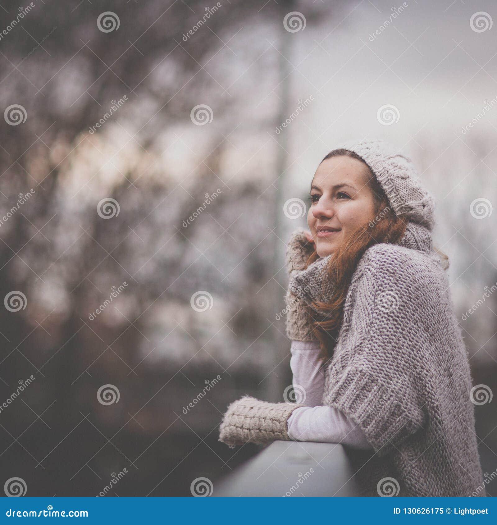 Retrato del otoño/del invierno: mujer joven vestida en una rebeca de lana caliente