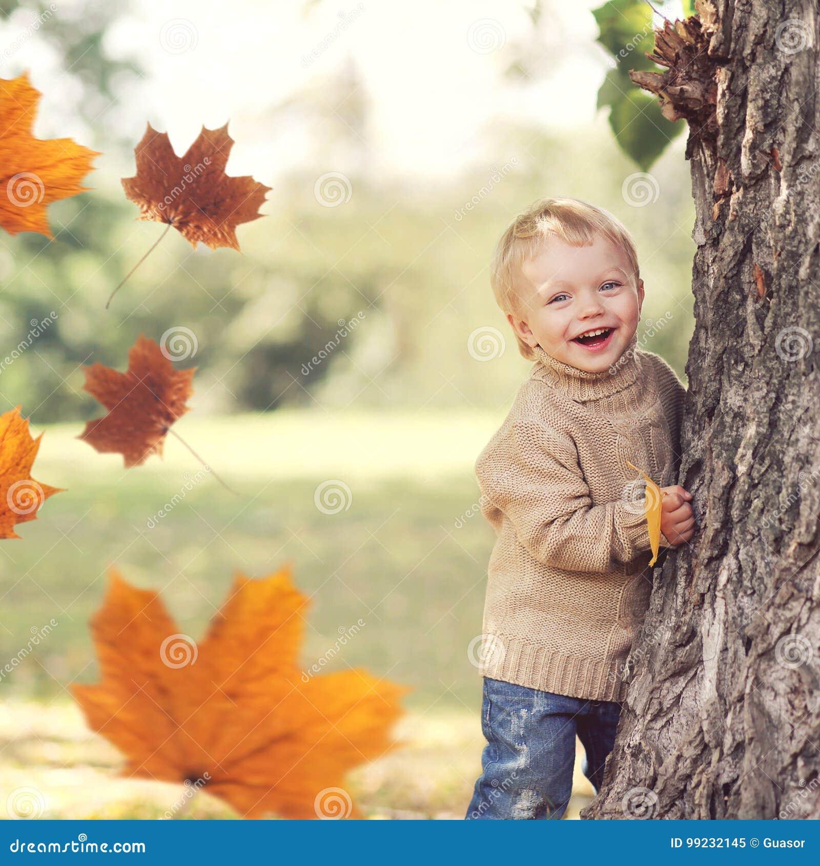 Retrato del otoño del niño feliz que juega divirtiéndose con volar las hojas de arce amarillas