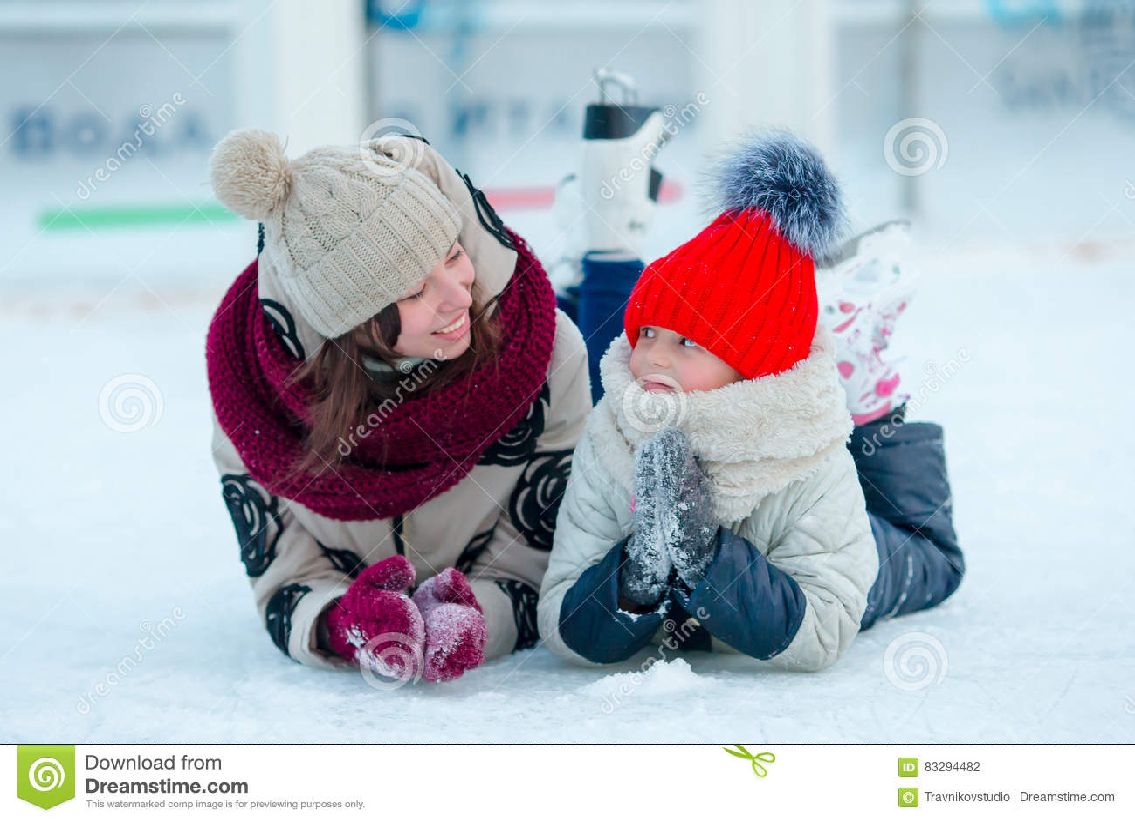 Retrato del patinaje de la pequeña muchacha adorable y de la mujer joven
