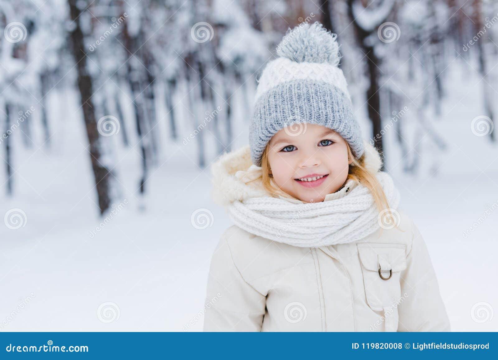 Retrato del pequeño niño lindo en sombrero y bufanda que sonríe en la cámara