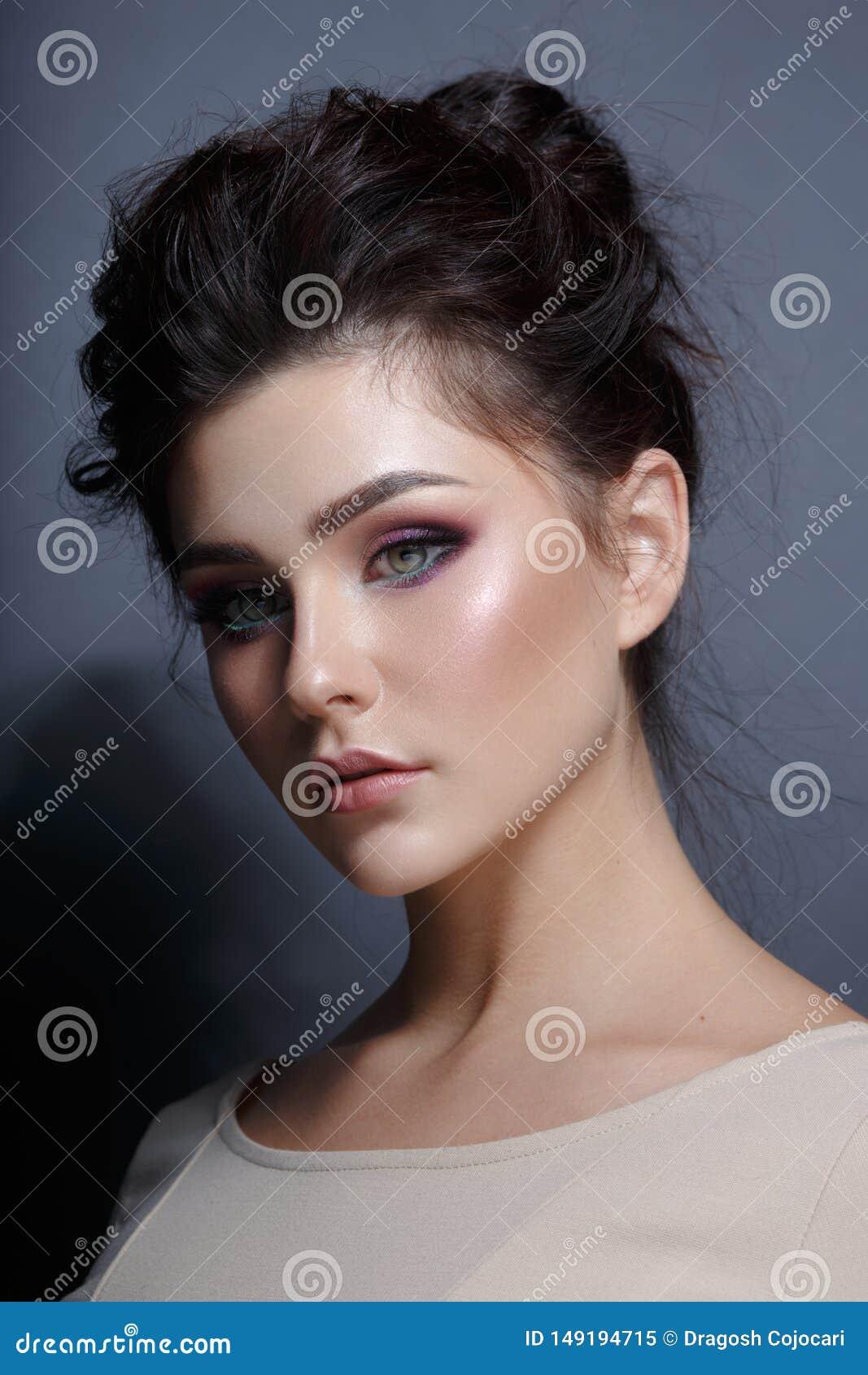 Retrato del perfil de una mujer agraciada con maquillaje del superbe, mirando la c?mara Visi?n vertical