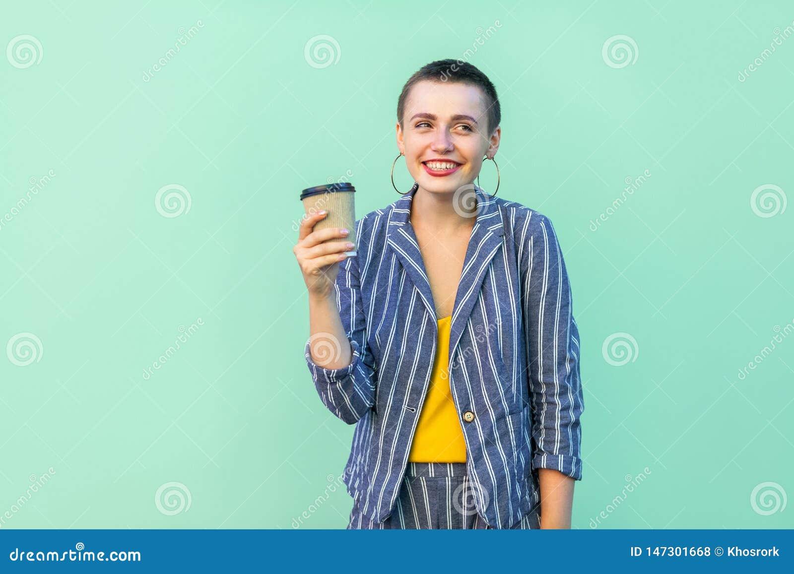 Retrato del positivo que descansa hermoso con la mujer joven en la situación rayada del traje, café de consumición del pelo corto