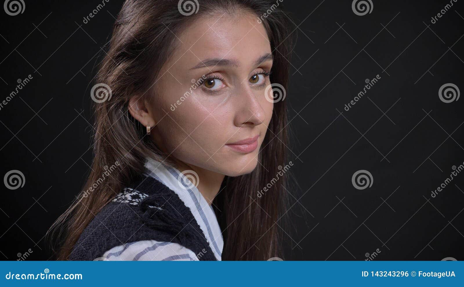 Retrato del primer de la cara femenina caucásica linda joven con los ojos marrones y el pelo moreno que miran de torneado a la cá