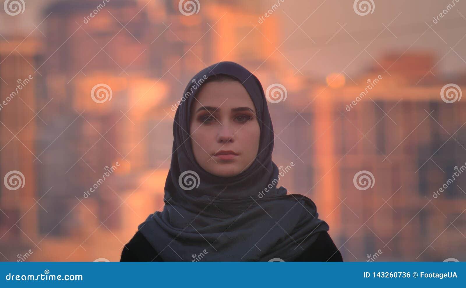 Retrato del primer de la hembra atractiva joven en el hijab que mira derecho la cámara con la ciudad urbana en el fondo