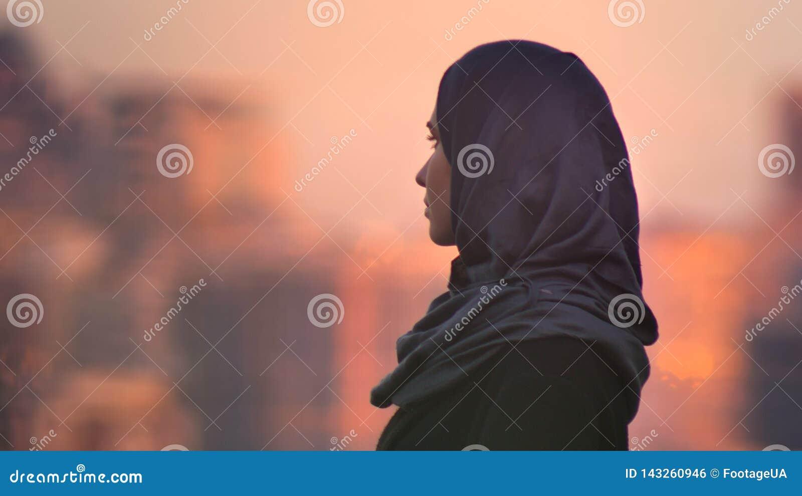 Retrato del primer de la hembra bonita joven en el hijab que mira adelante con el ambiente urbano y los edificios brillantes en