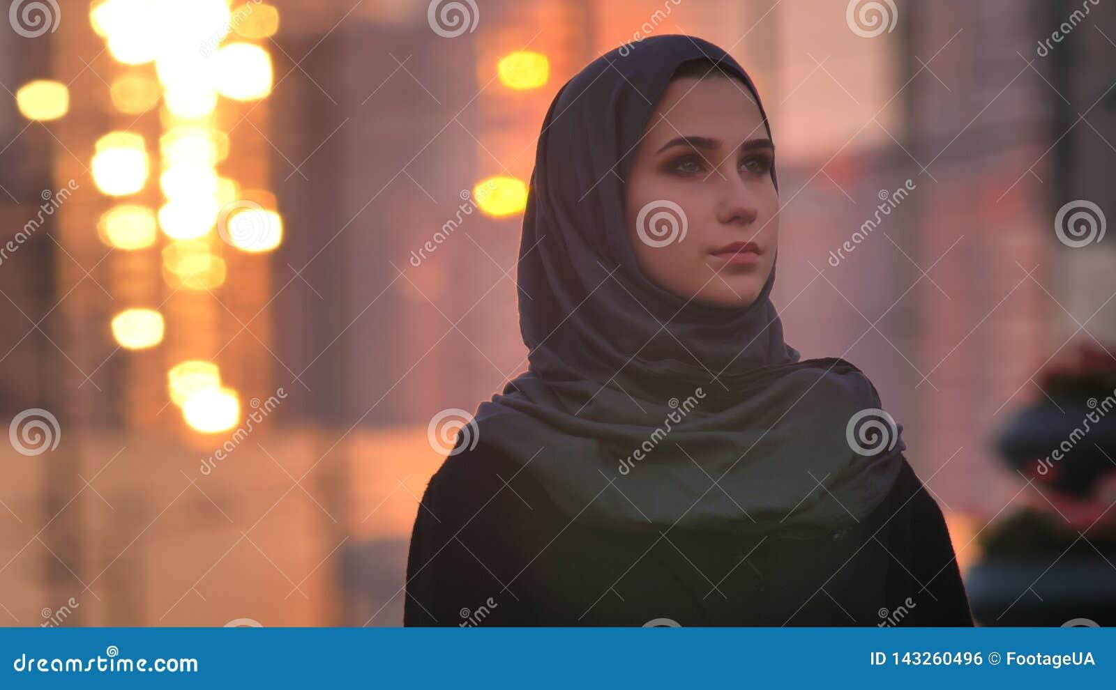 Retrato del primer de la hembra bonita joven en el hijab que parece directo con la ciudad urbana y los edificios brillantes en