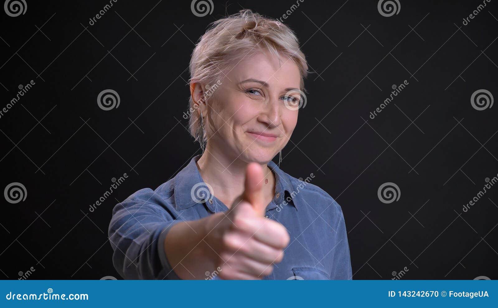 Retrato del primer de la hembra caucásica atractiva adulta que sonríe alegre y que gesticula el pulgar para arriba mientras que m