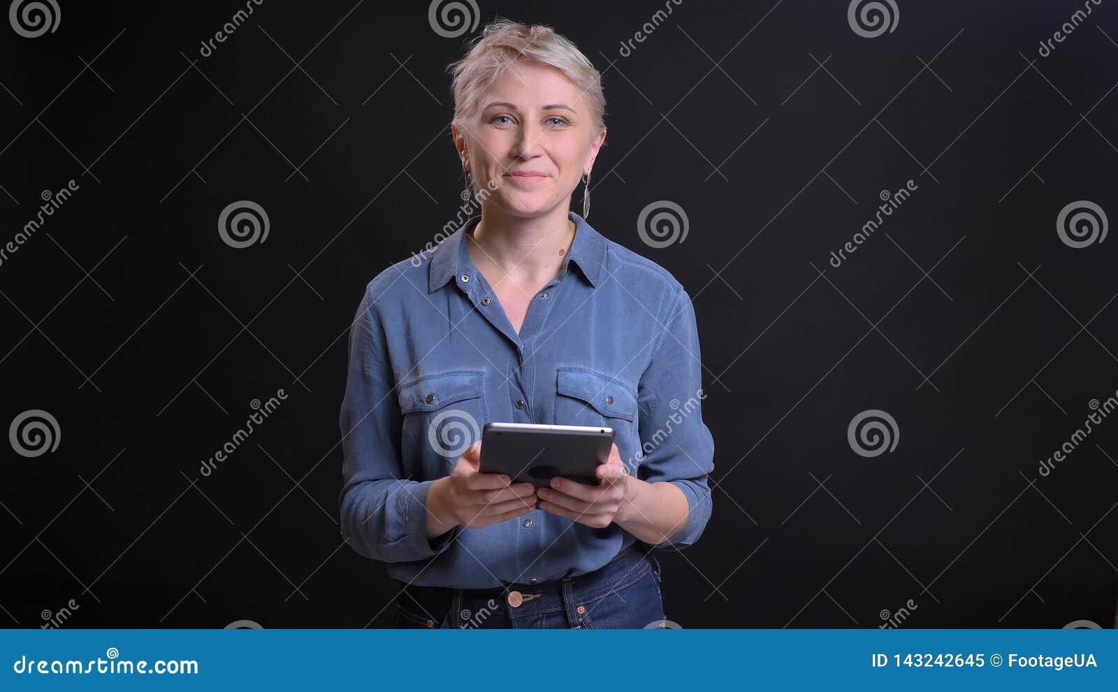 Retrato del primer de la hembra caucásica bonita adulta con el pelo rubio corto usando la tableta que mira la cámara y la sonrisa