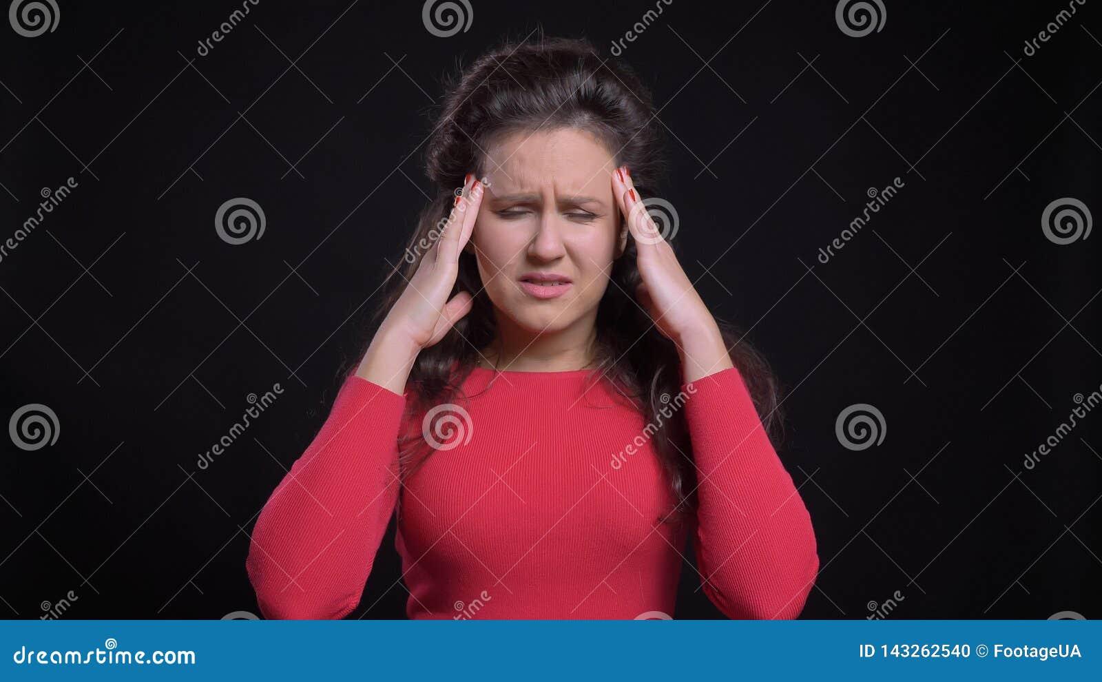 Retrato del primer de la hembra caucásica de mediana edad atractiva que tiene un dolor de cabeza delante de la cámara con el fond