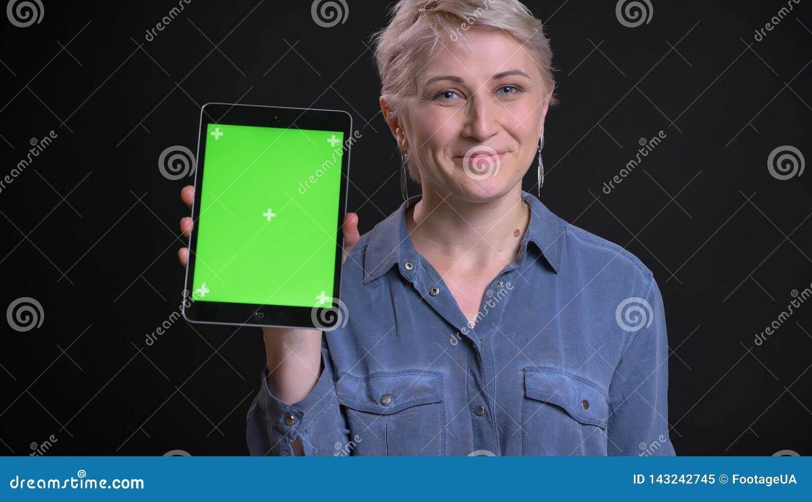 Retrato del primer de la hembra caucásica sonriente adulta con el pelo rubio corto usando la tableta y mostrar la pantalla verde