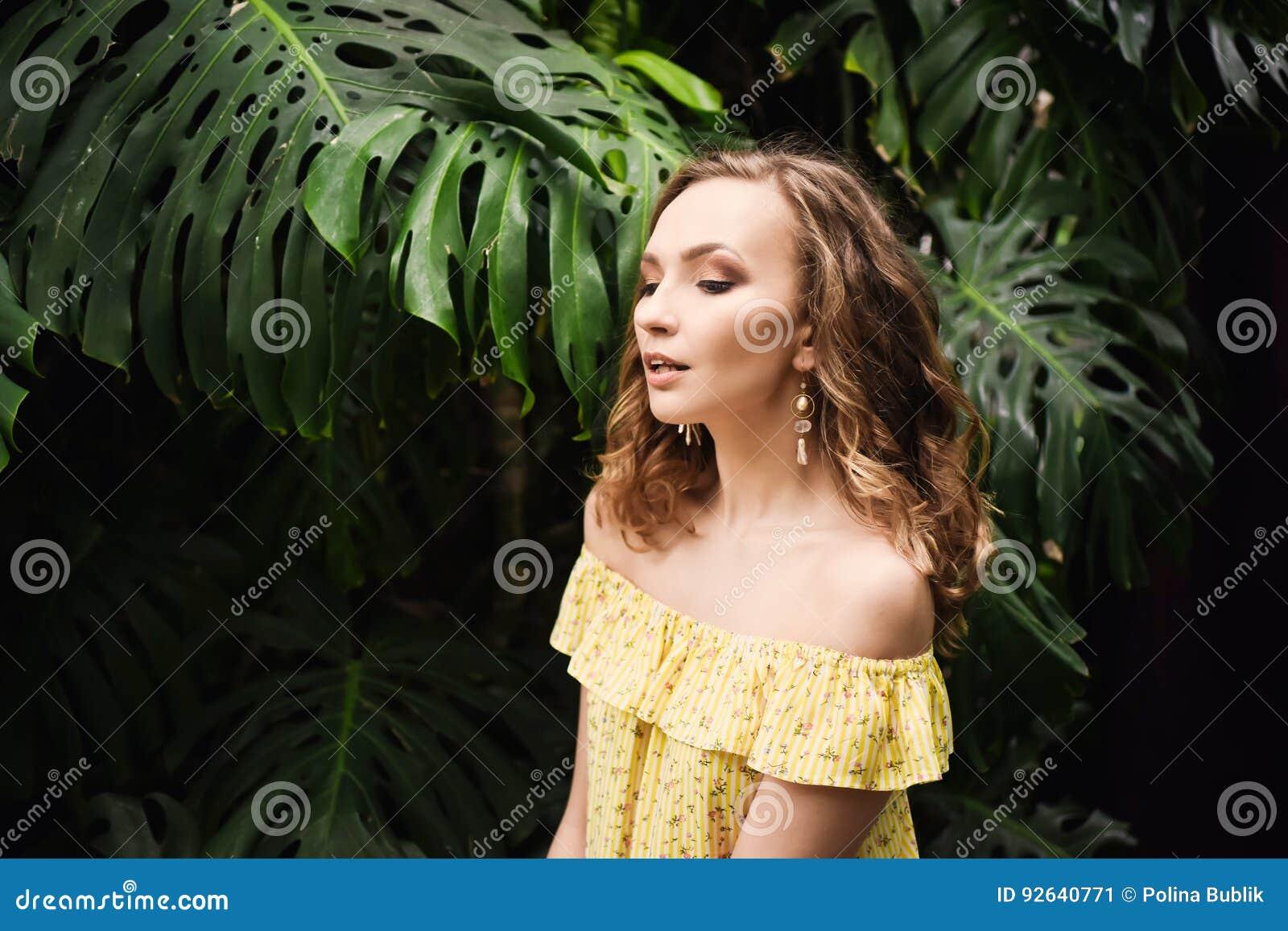 Retrato del primer de la muchacha hermosa joven con el vestido del verano del pelo rizado en bosque tropical