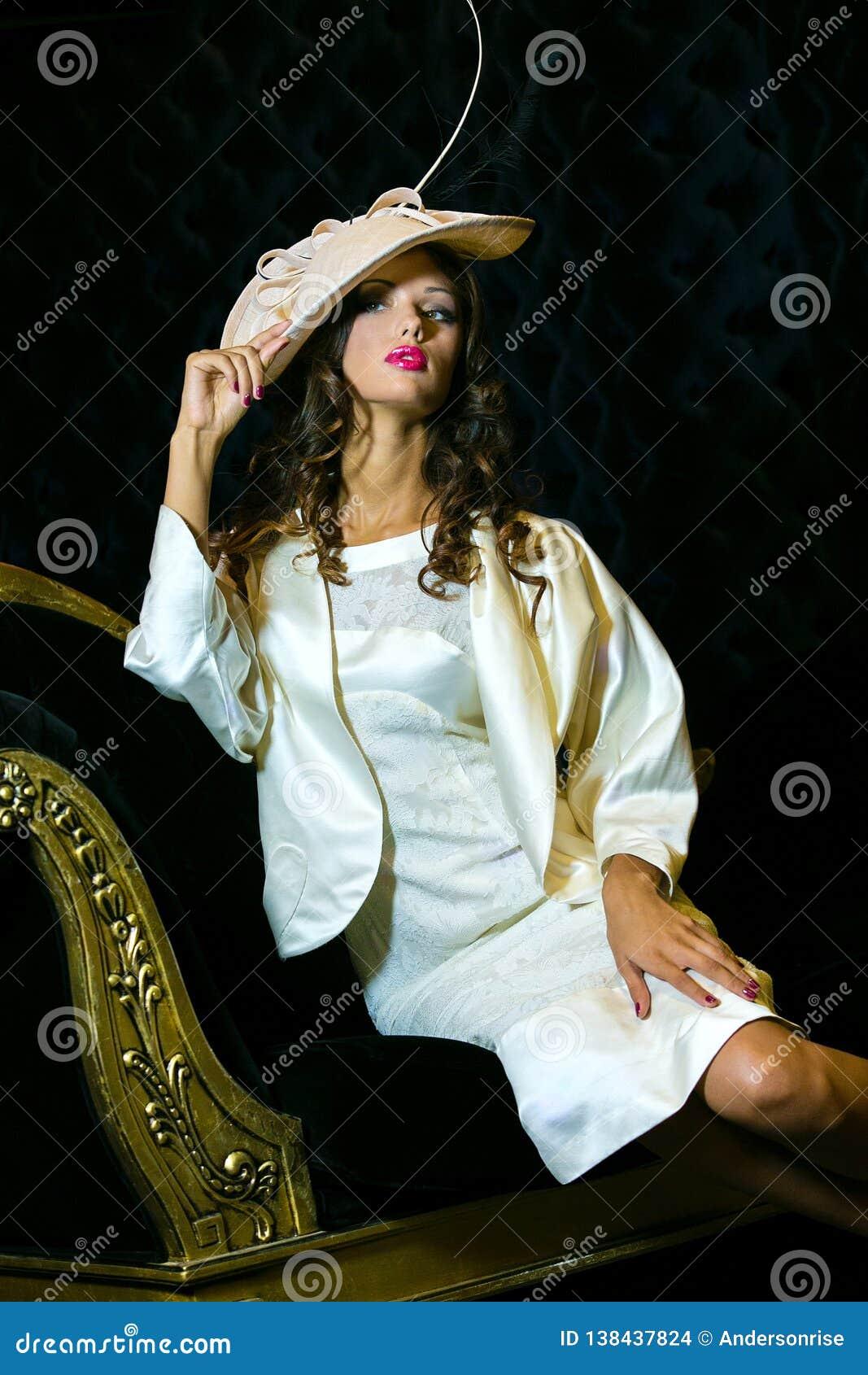 Retrato del primer de la mujer hermosa joven en un ehat del diseñador