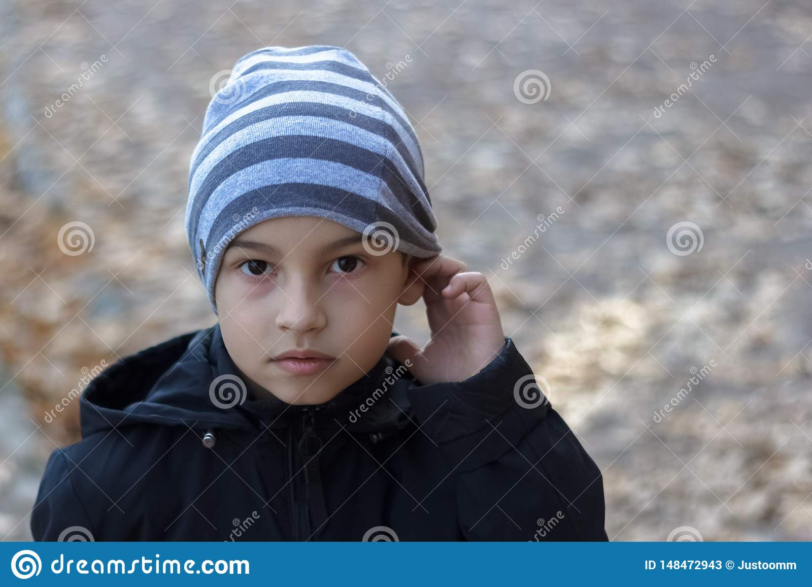 Retrato del primer de un niño pobre con problemas de la audiencia, llevando a cabo su mano cerca de su oído, mostrándome que él n