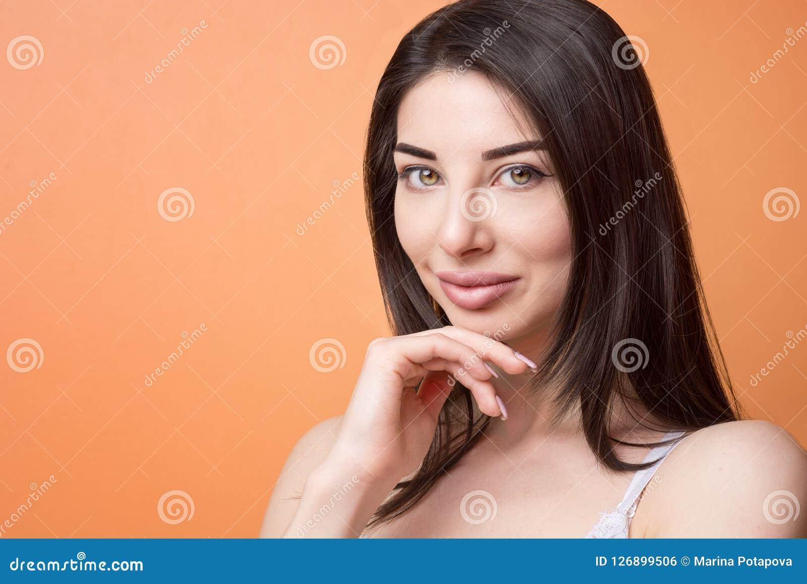 Retrato del primer de una mujer pensativa morena hermosa feliz joven