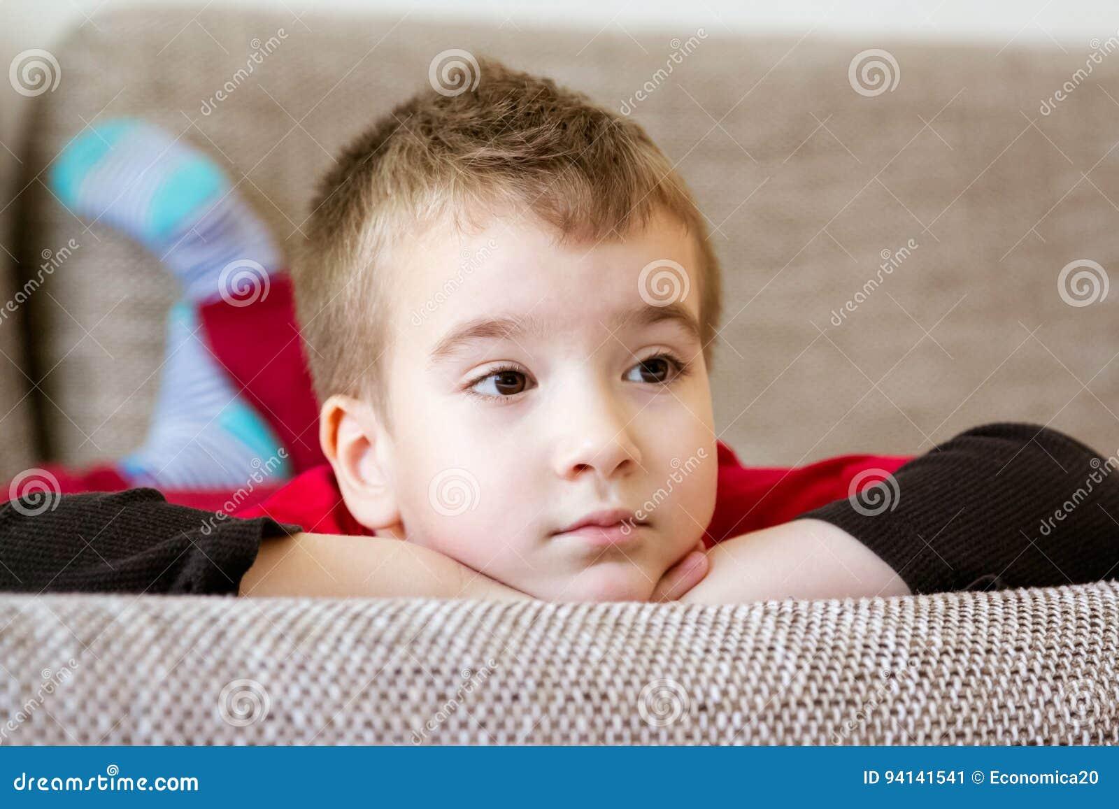 Retrato del primer del niño pequeño adorable que descansa sobre el sofá