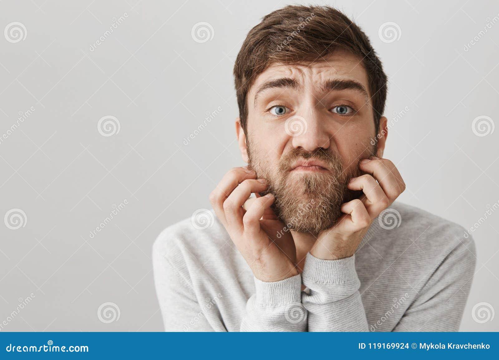 Retrato del primer del hombre adulto sin afeitar torpe que rasguña la barba mientras que mira con mirada insatisfecha la cámara c