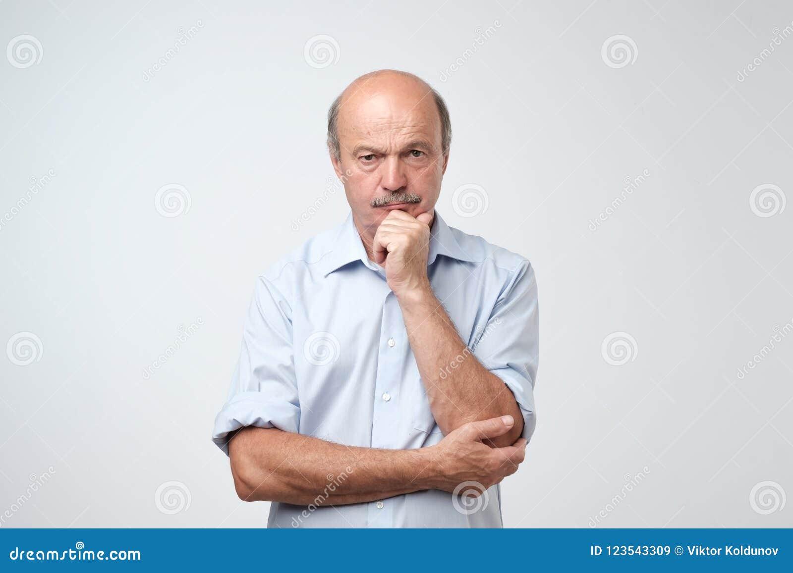 Retrato del primer del hombre maduro soñoliento en la camisa azul, individuo divertido que pone la cabeza a mano, en cámara de mi
