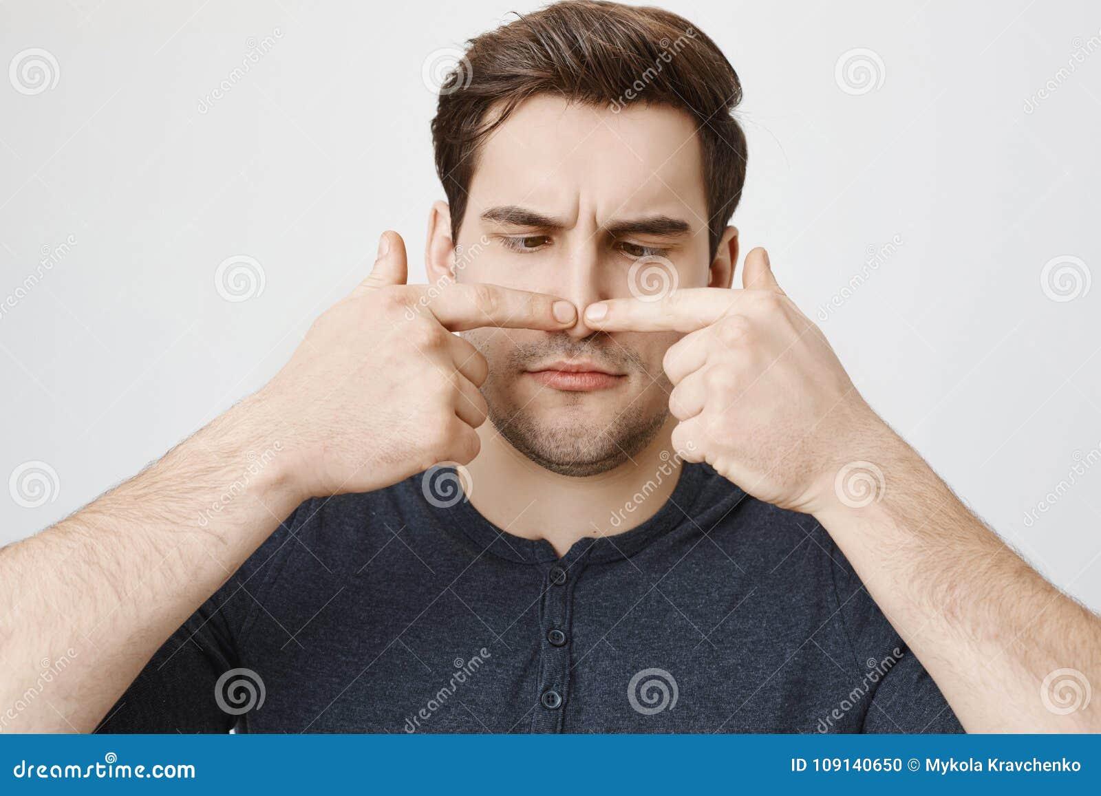 Retrato del primer del individuo divertido con el corte de pelo lindo que toca su nariz con ambos dedos índices y que la mira, co