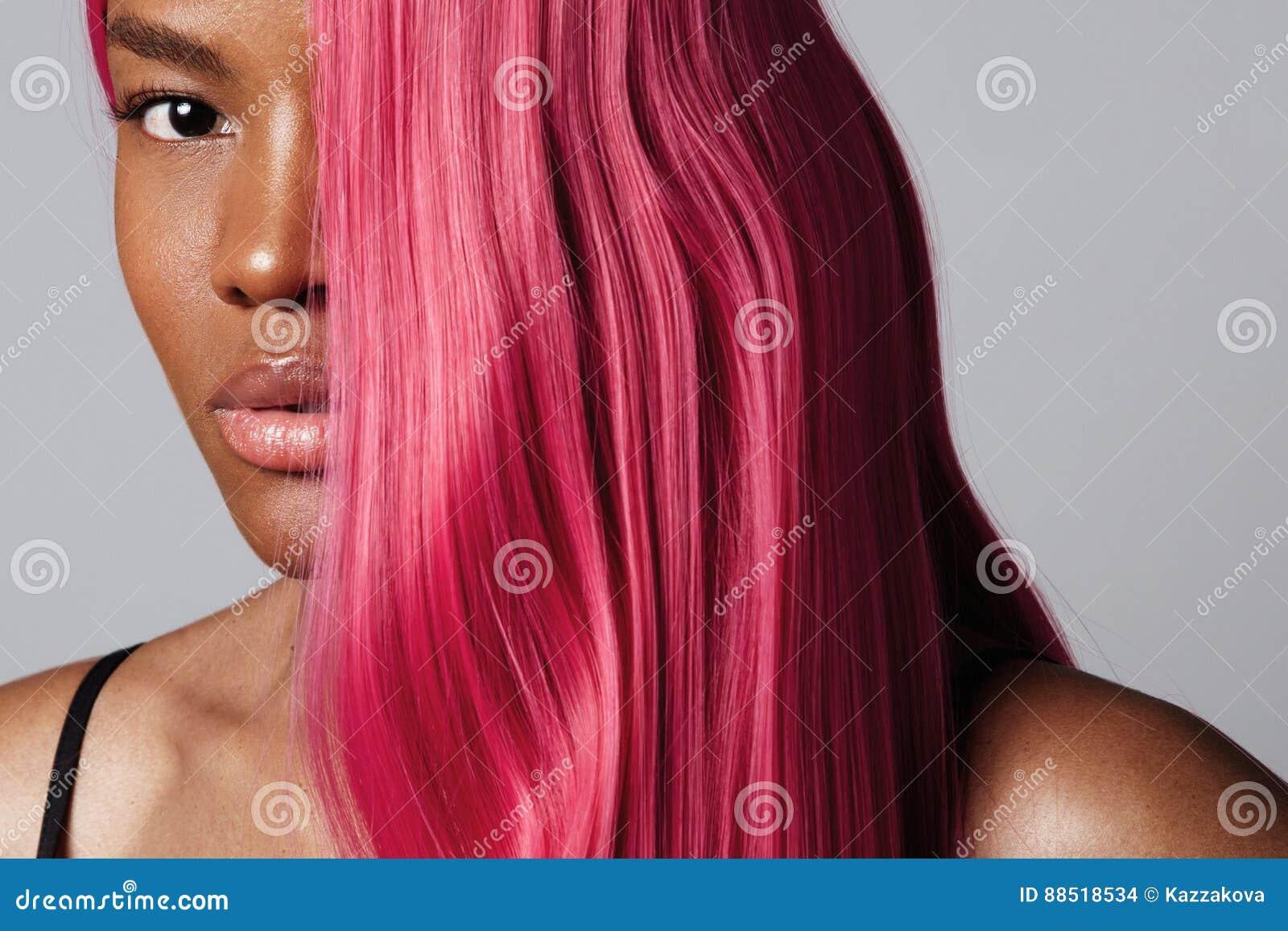 Retrato del ` s de la mujer con una mitad de una cara cubierta por el pelo rosado