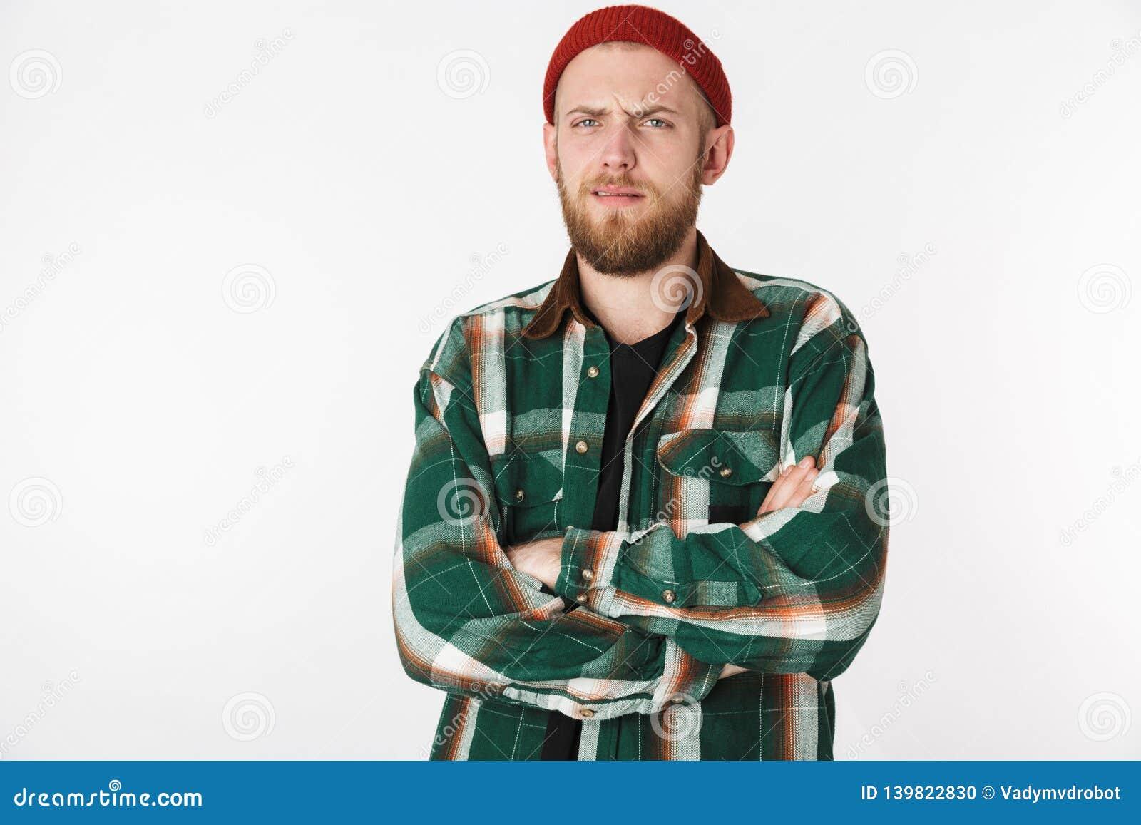 Retrato del sombrero del individuo barbudo atractivo y de la camisa de tela escocesa que llevan, colocándose aislado sobre el fon