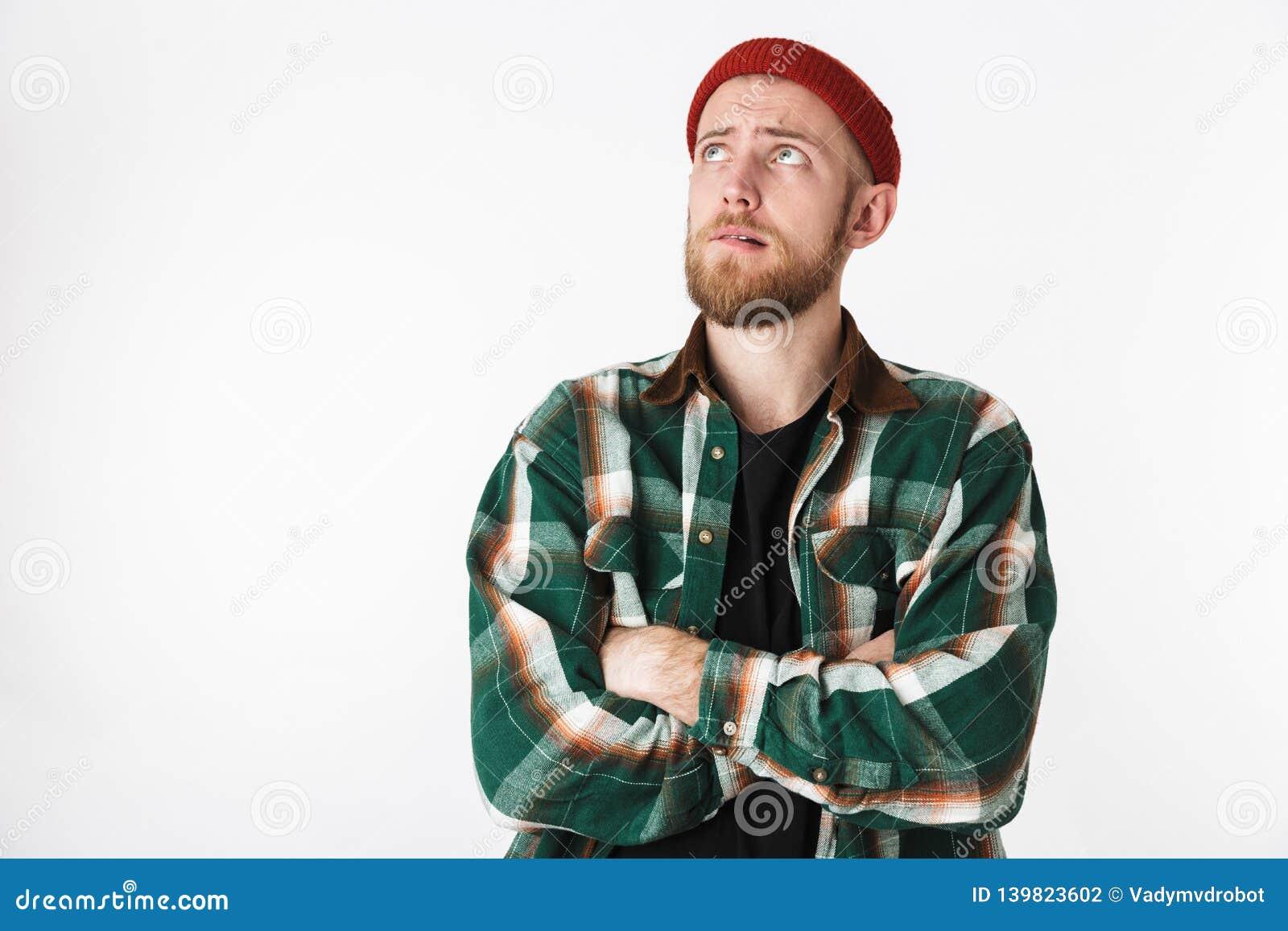 Retrato del sombrero del individuo barbudo joven y de la camisa de tela escocesa que llevan que miran para arriba, mientras que s