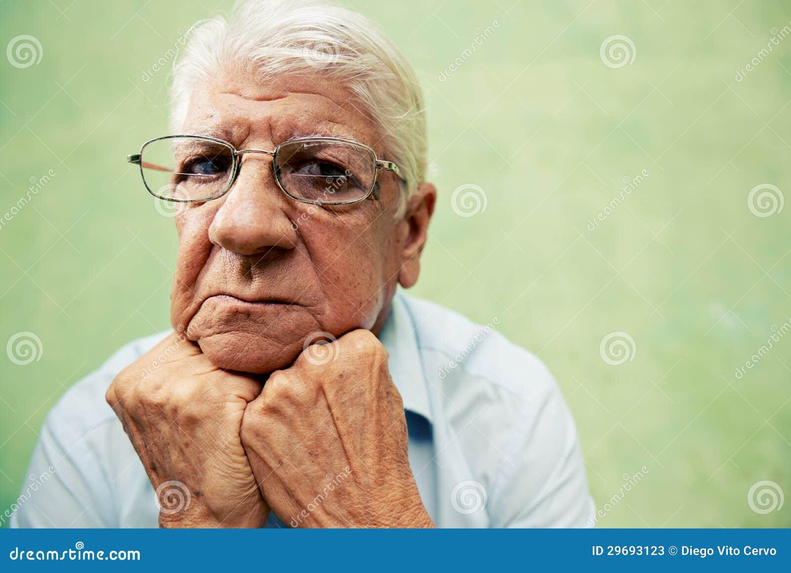 Retrato del viejo hombre serio que mira la cámara con las manos en la barbilla