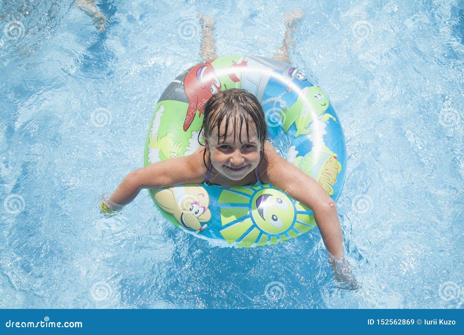 Retrato divertido de la muchacha linda feliz del peque?o ni?o que juega con el anillo colorido en piscina Los ni?os aprenden nada