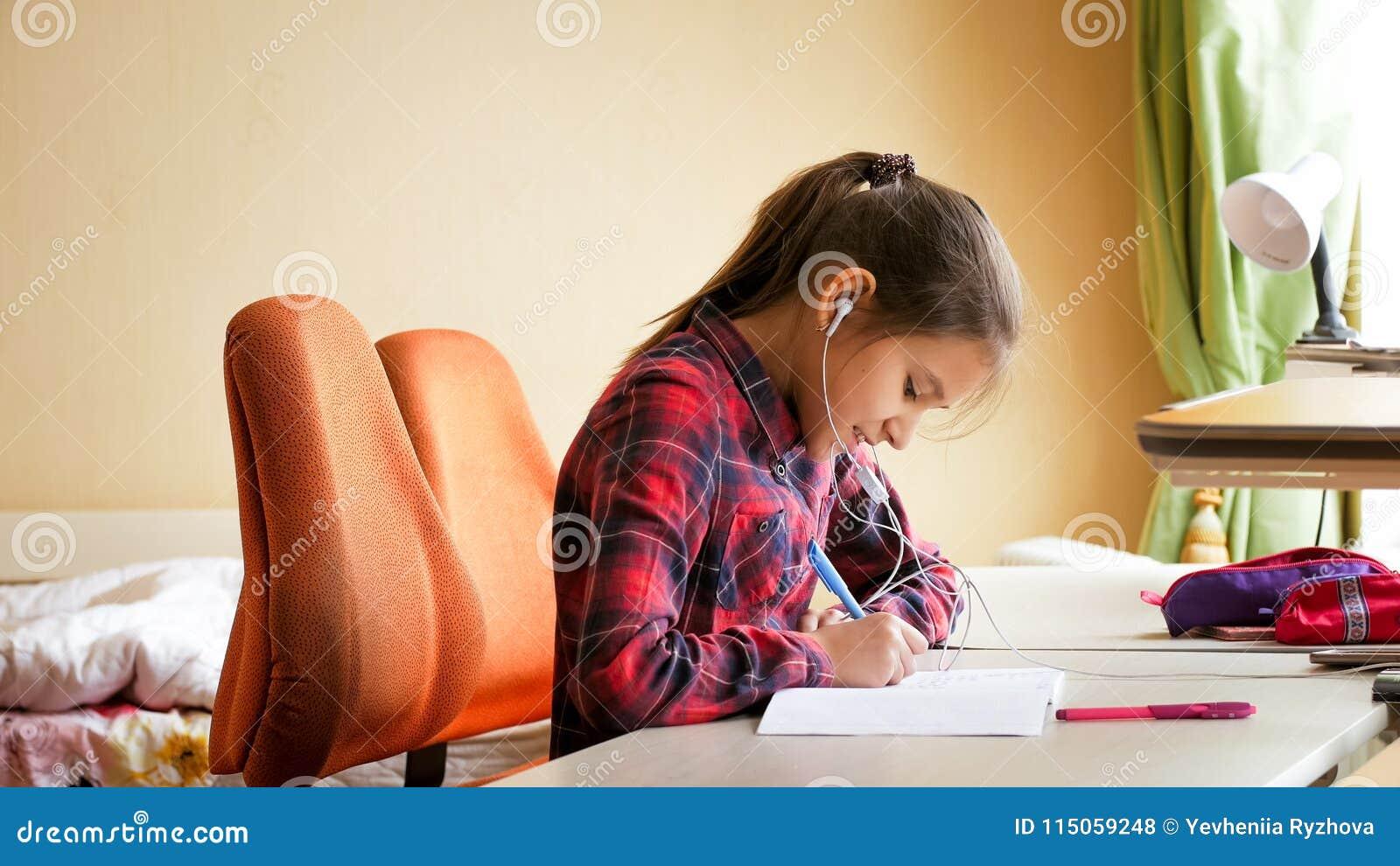 Retrato do adolescente de sorriso que faz trabalhos de casa e a música de escuta