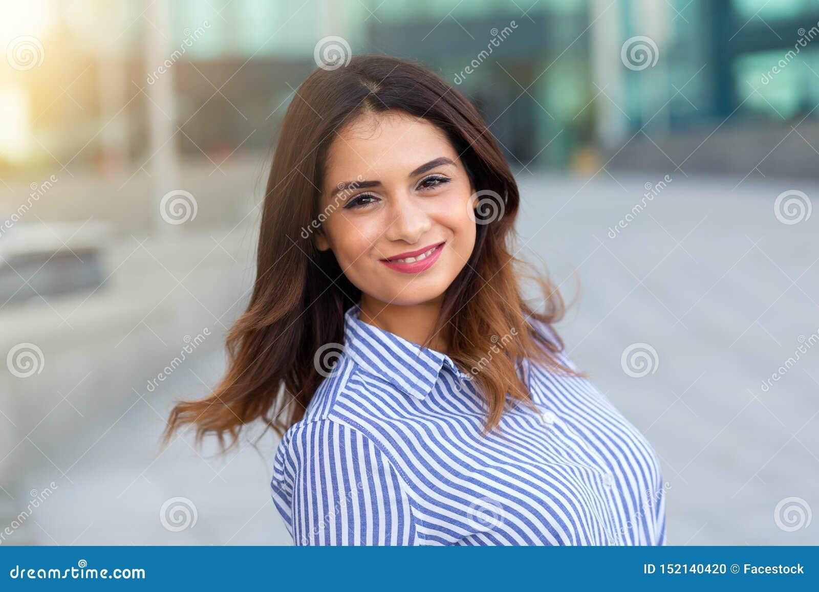 Retrato do ar livre de sorriso novo da mulher com alargamento do sunligth