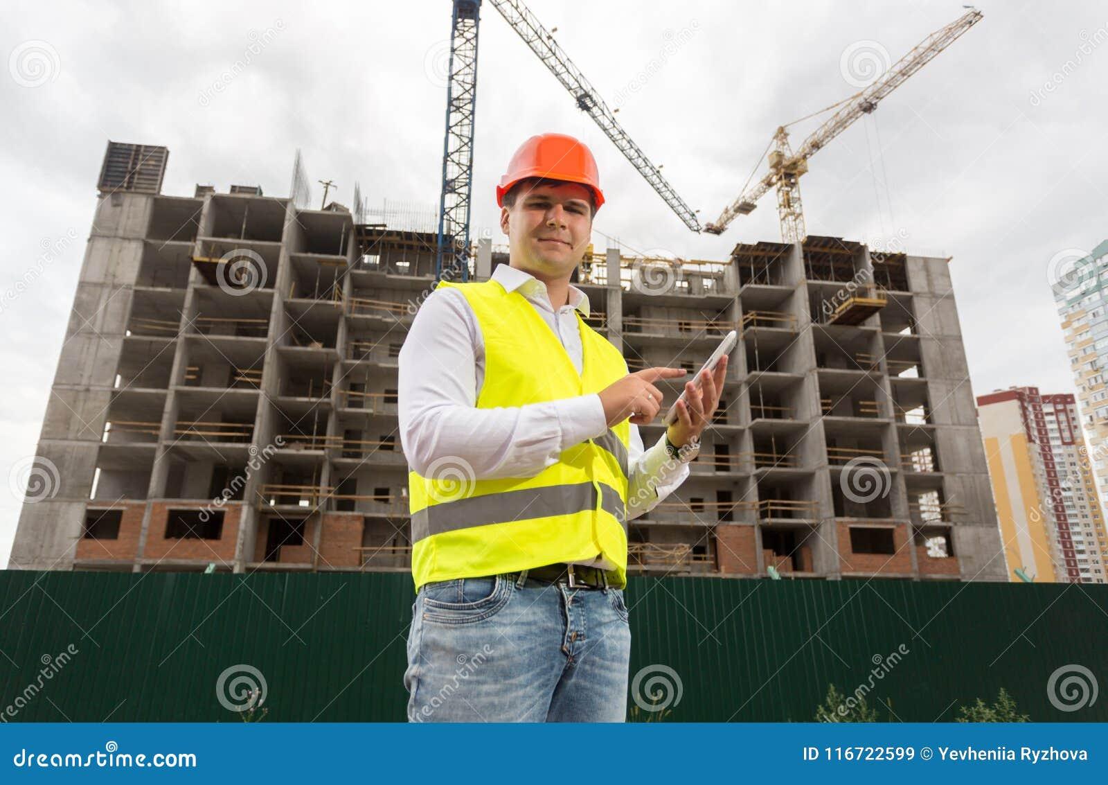 Retrato do arquiteto masculino de sorriso que usa a tabuleta digital no terreno de construção