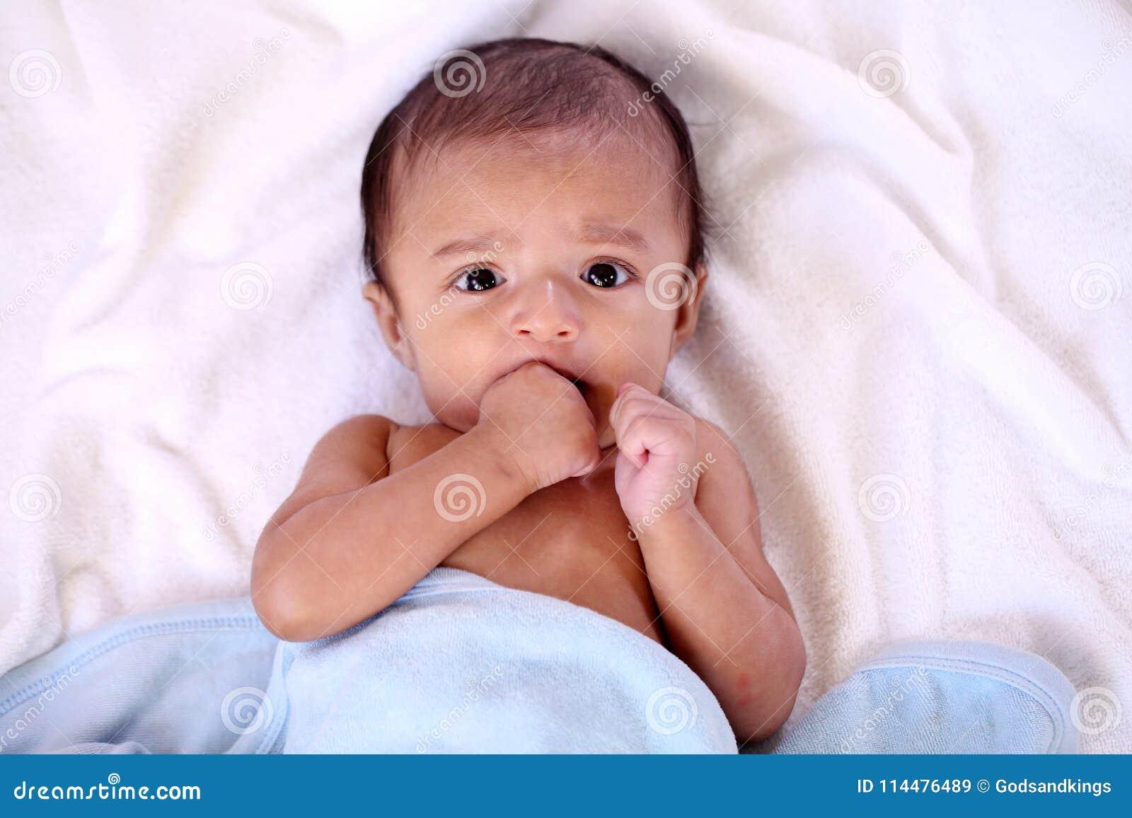 Retrato do bebê recém-nascido que sai os dentes e para sugar o reflexo