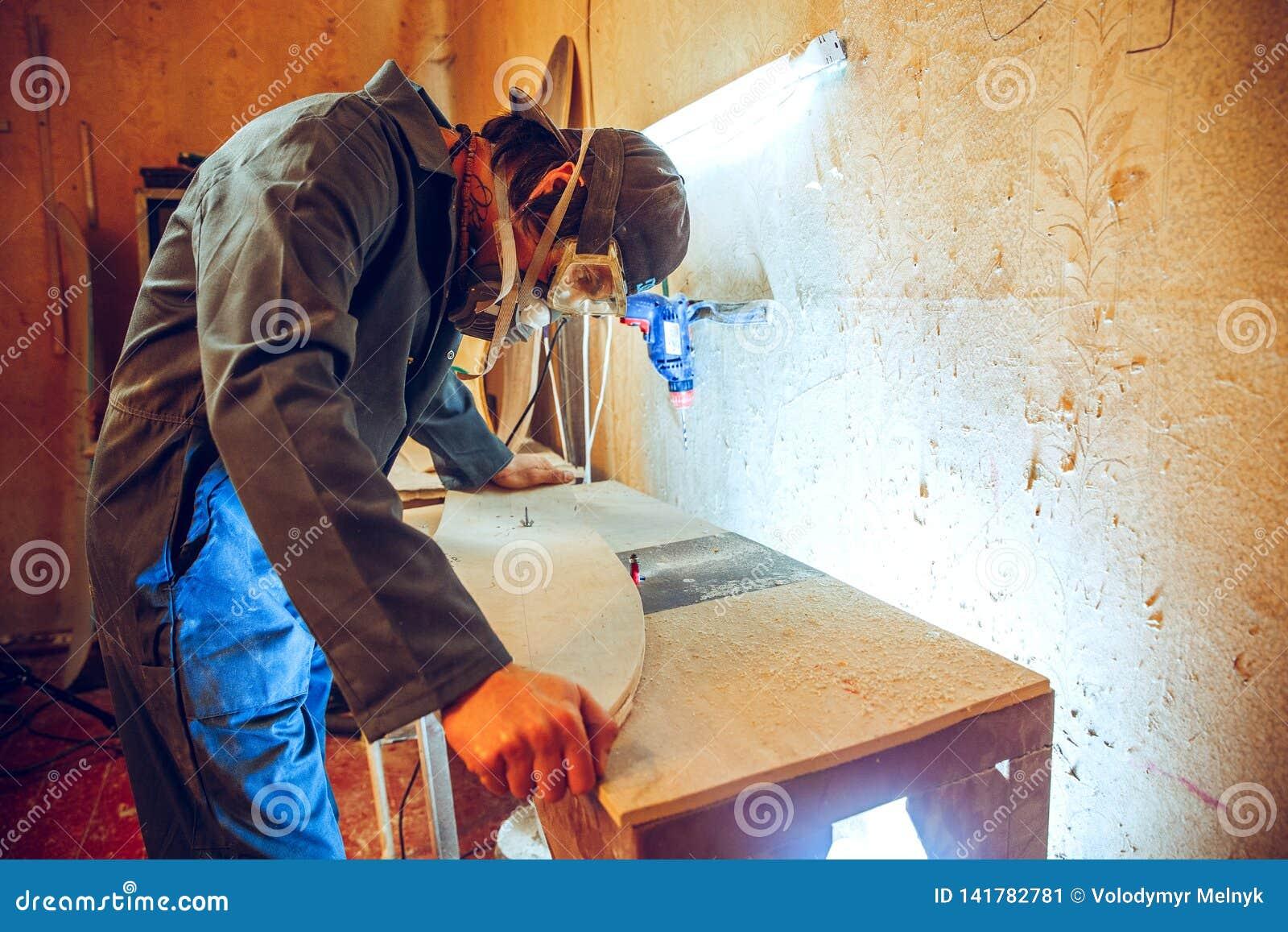 Retrato do carpinteiro considerável que trabalha com o patim na oficina