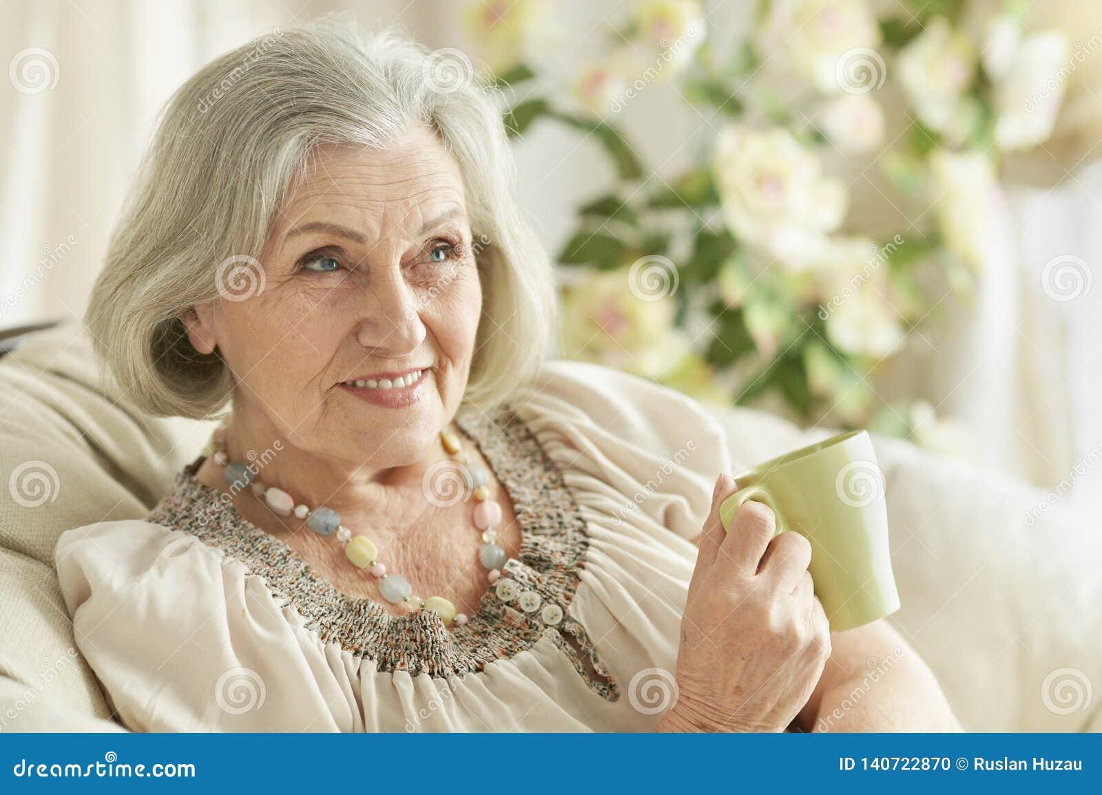 Retrato do chá bebendo da mulher superior feliz ao descansar em casa