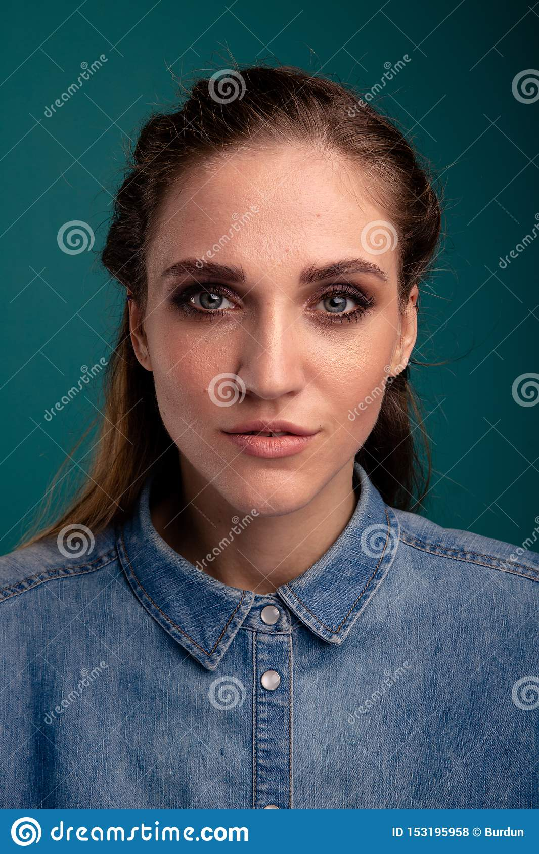 Retrato do close up da jovem mulher bonita que levanta em um estúdio isolado sobre o fundo azul