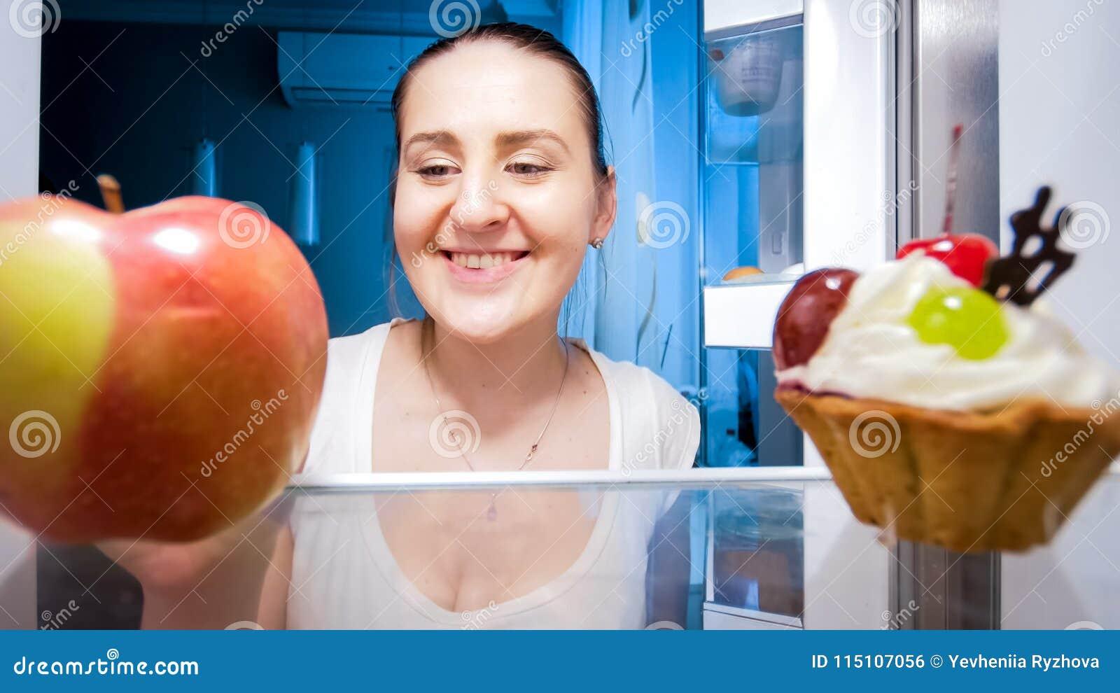 Retrato do close up da jovem mulher de sorriso que duvida entre comer a maçã ou o bolo na noite