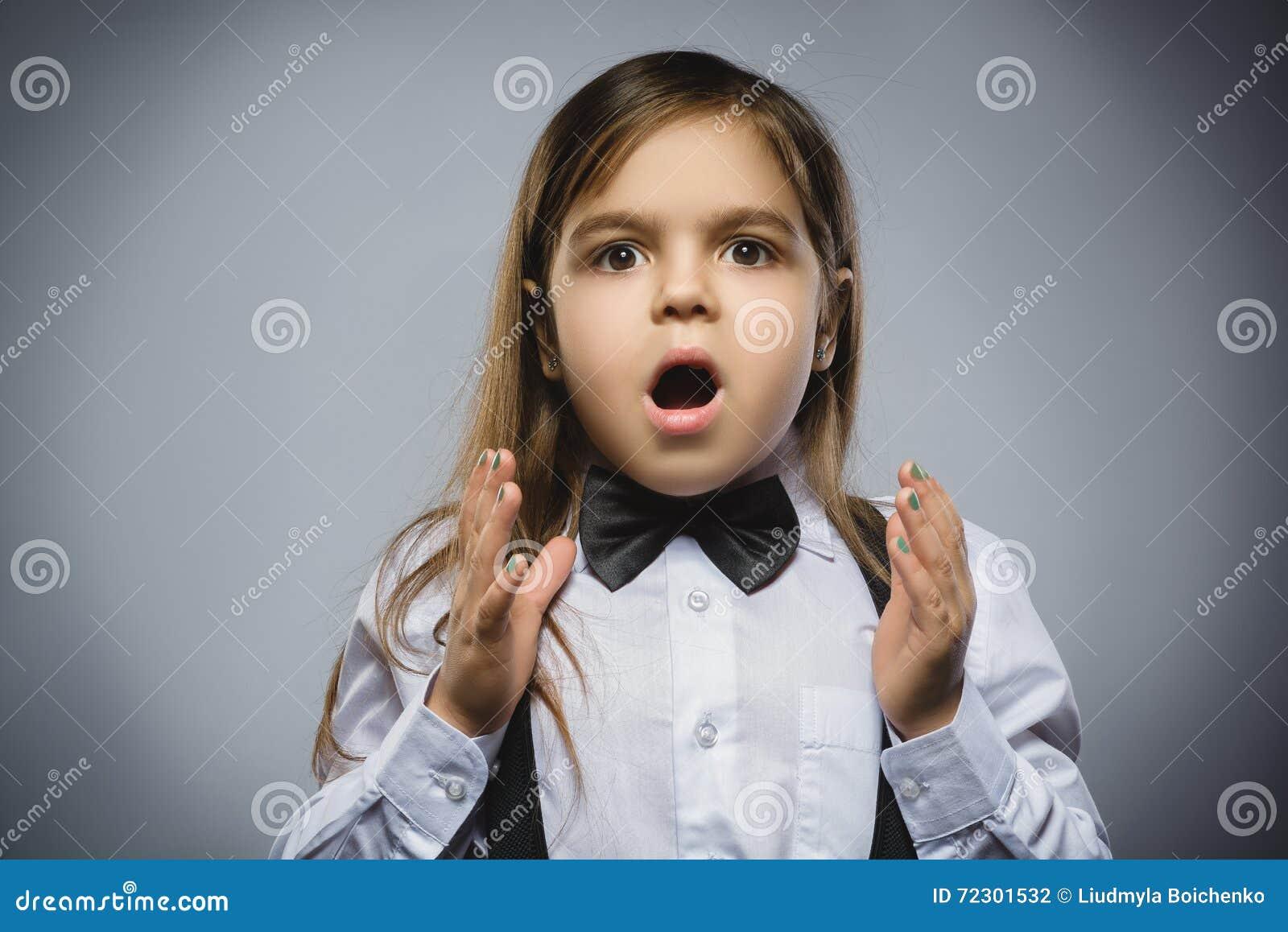 Retrato do close up da menina considerável com expressão surpreendida ao estar contra o fundo cinzento