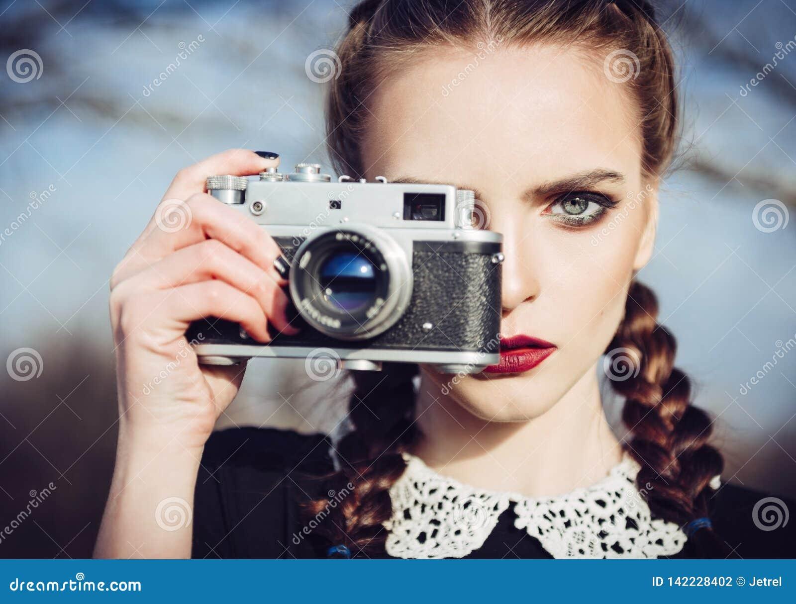 Retrato do close-up da moça bonita com a câmera velha do filme à disposição