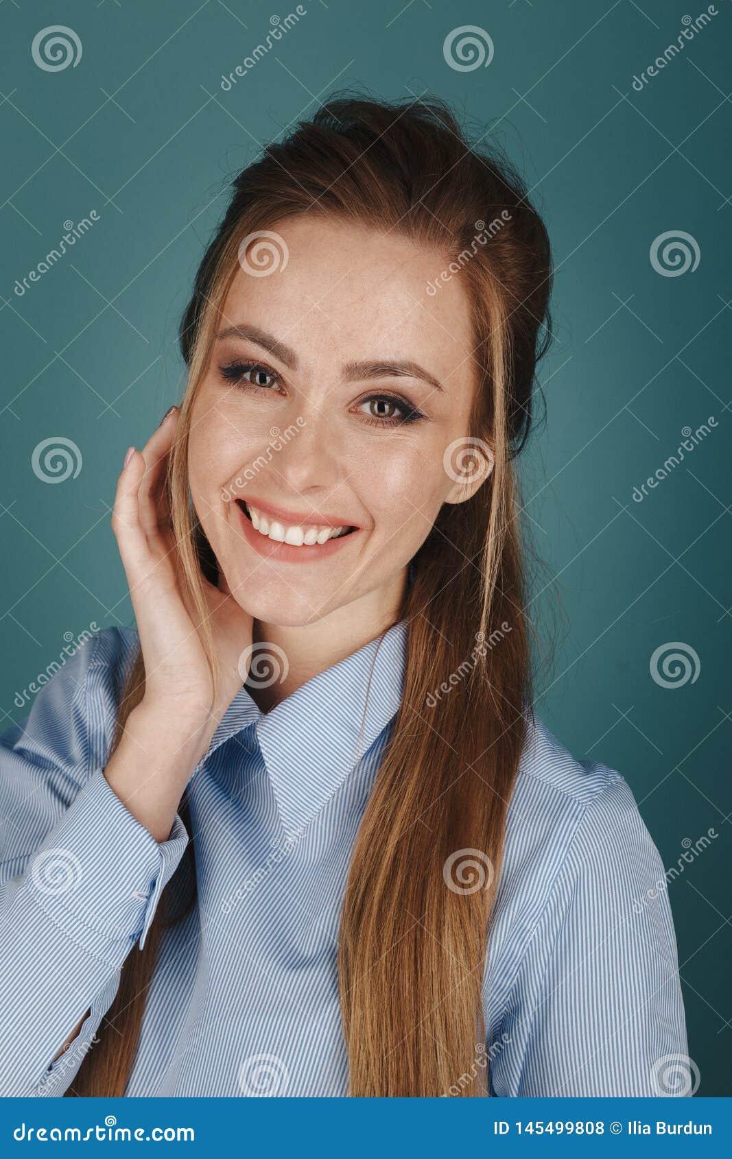 Retrato do close up da mulher bonita de Yong com composição brilhante em um estúdio sobre o fundo azul