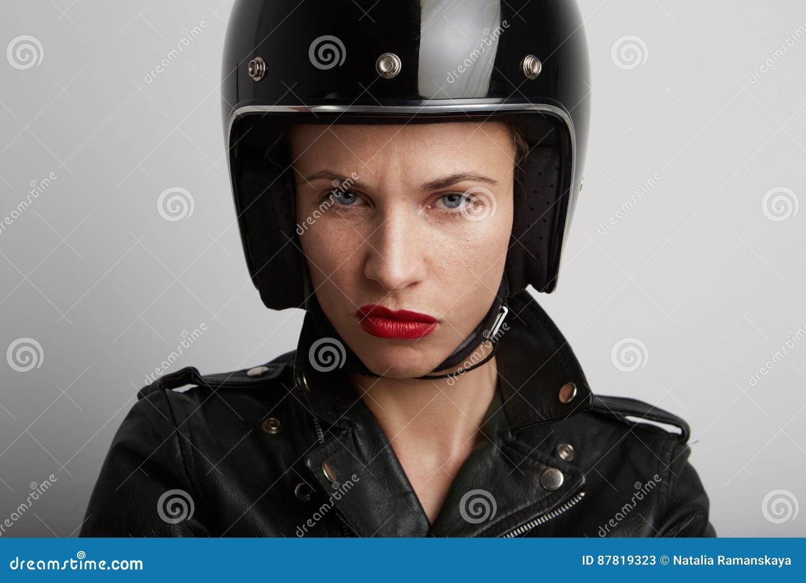 Retrato do close up da mulher do motociclista sobre o fundo branco, o capacete desportivo preto à moda vestindo e o casaco de cab