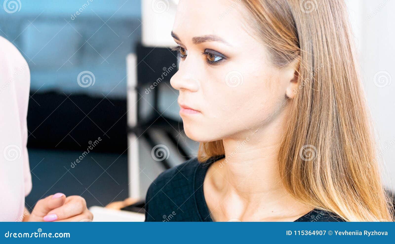 Retrato do close up da mulher loura nova que senta-se na cadeira no salão de beleza