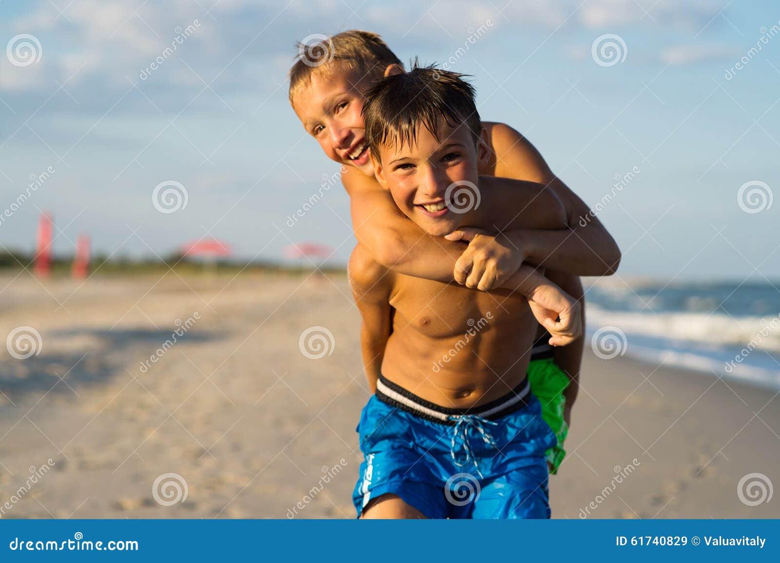 Retrato do close up de dois adolescentes felizes que jogam na praia do mar