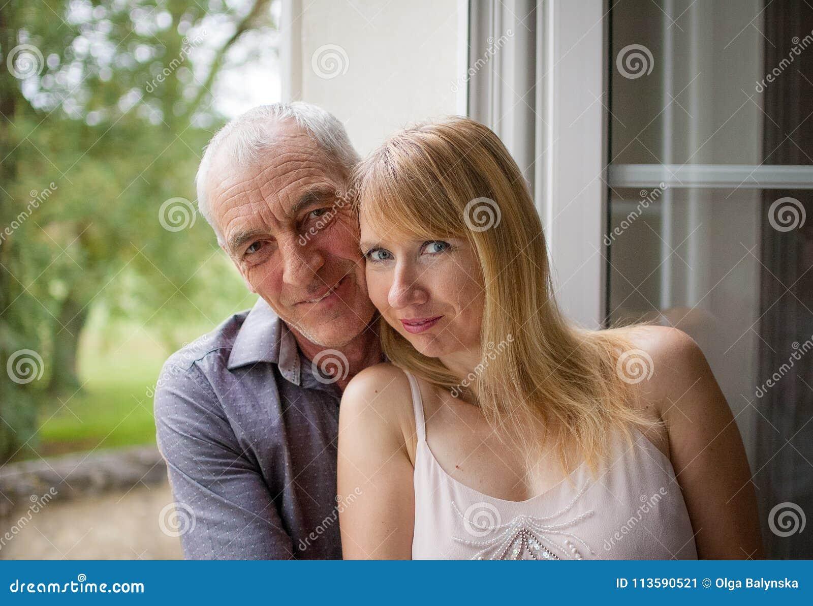 Retrato do close up de pares felizes com a diferença da idade que abraça perto da janela em sua casa durante o dia quente do verã