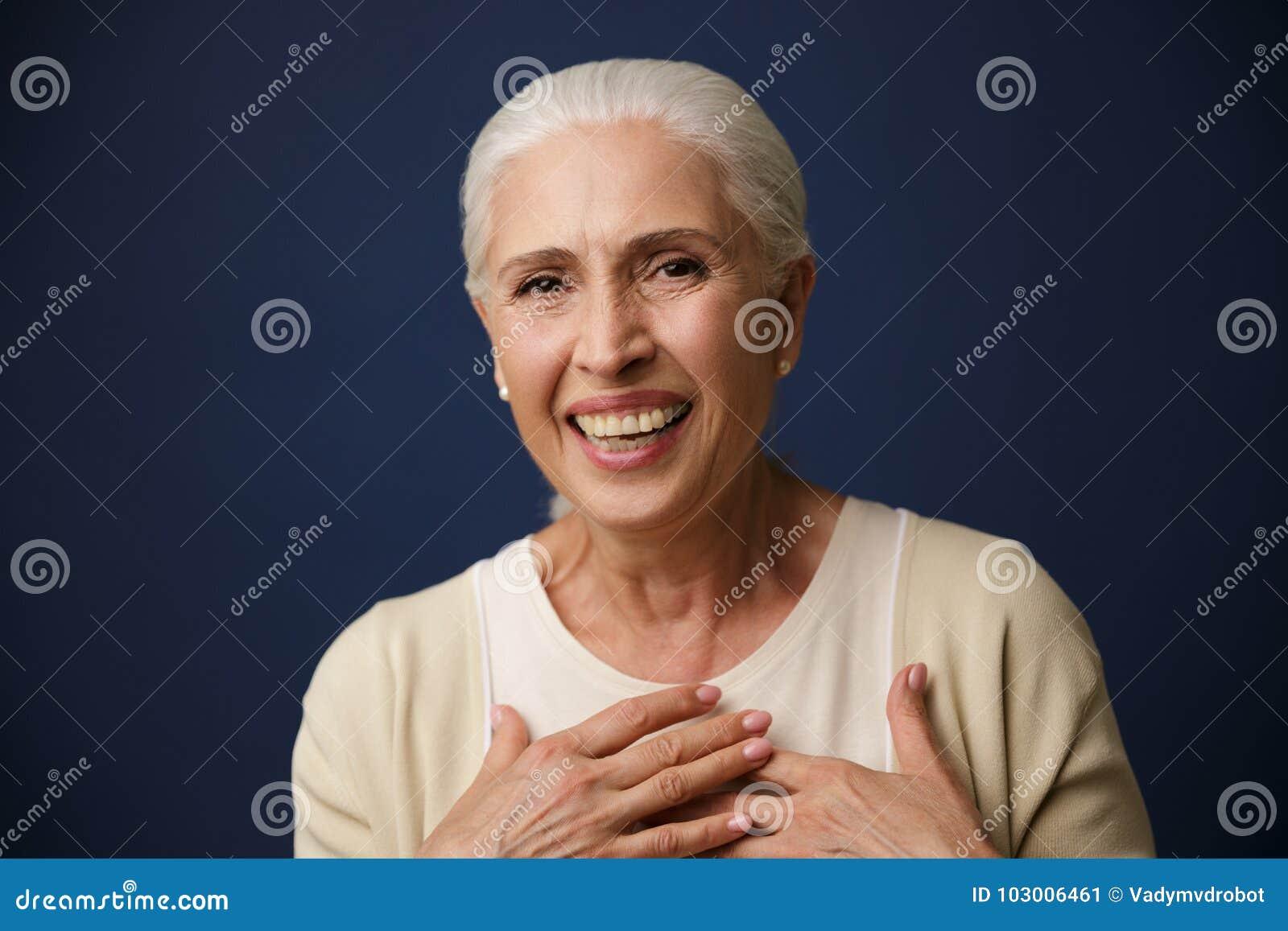 Retrato do close-up de rir a mulher madura, guardando as mãos nela