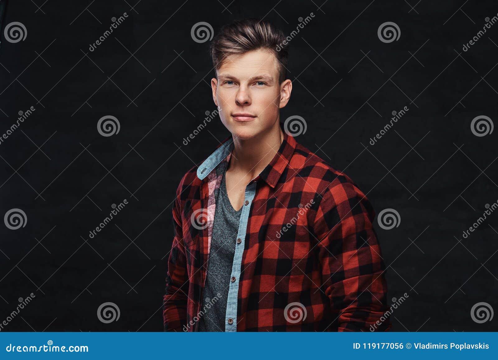 Retrato do close-up de um homem novo considerável em uma camisa do velo, levantando em um estúdio