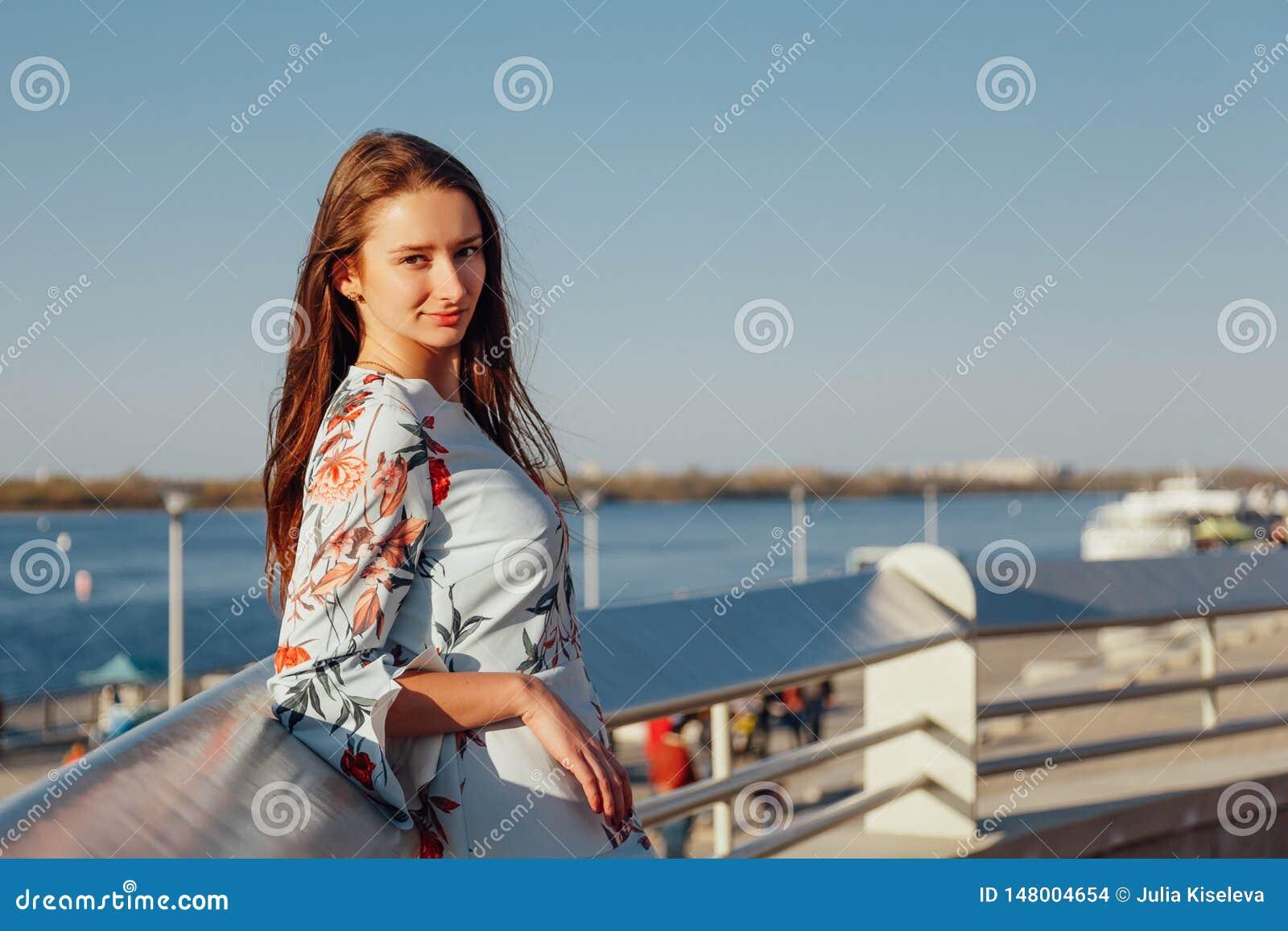 Retrato do close-up de uma jovem mulher com cabelo louro longo, vestido em um vestido elegante azul