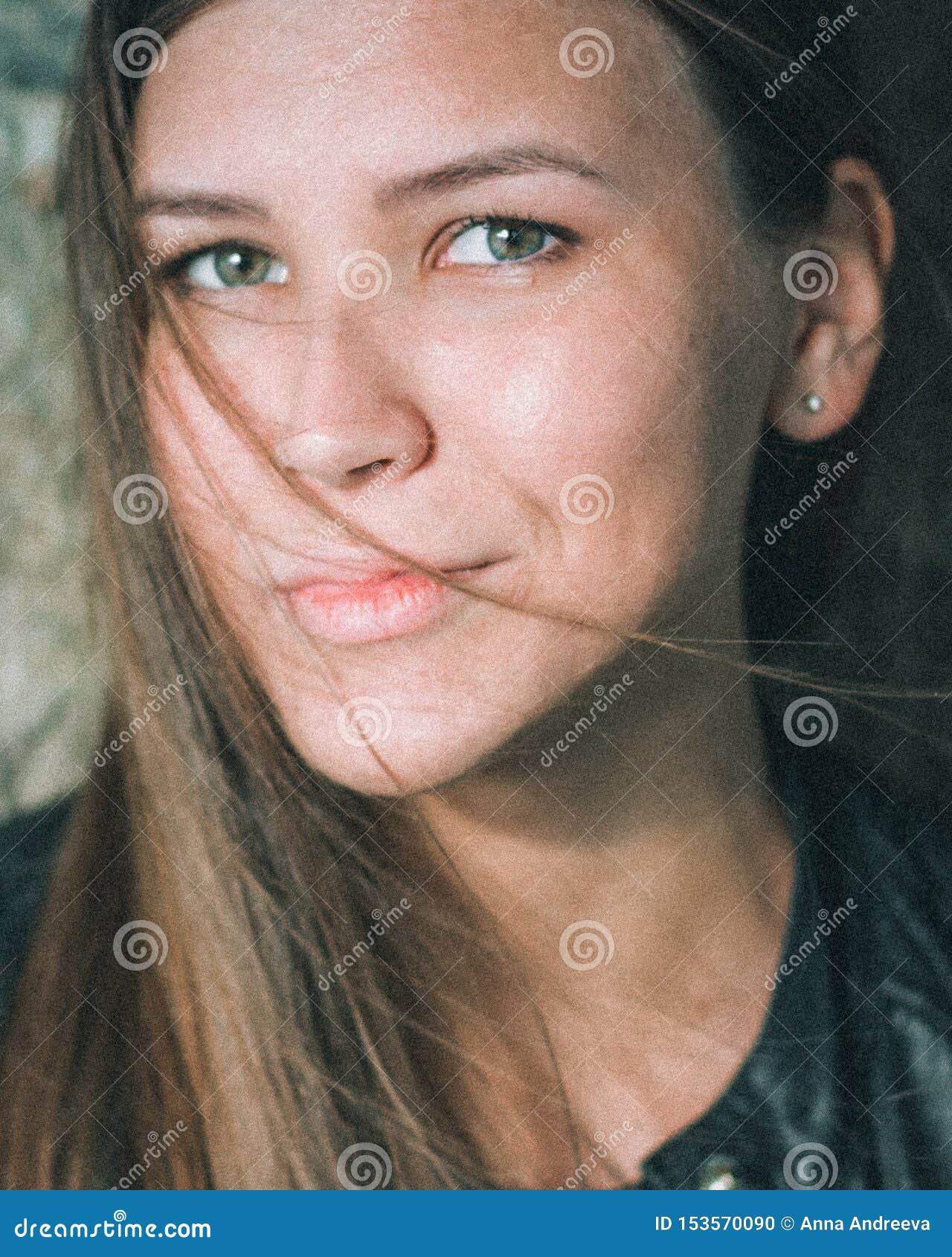 Retrato do close-up de uma menina caucasiano bonita com cabelo de fluxo louro longo Uma jovem mulher olha em linha reta no