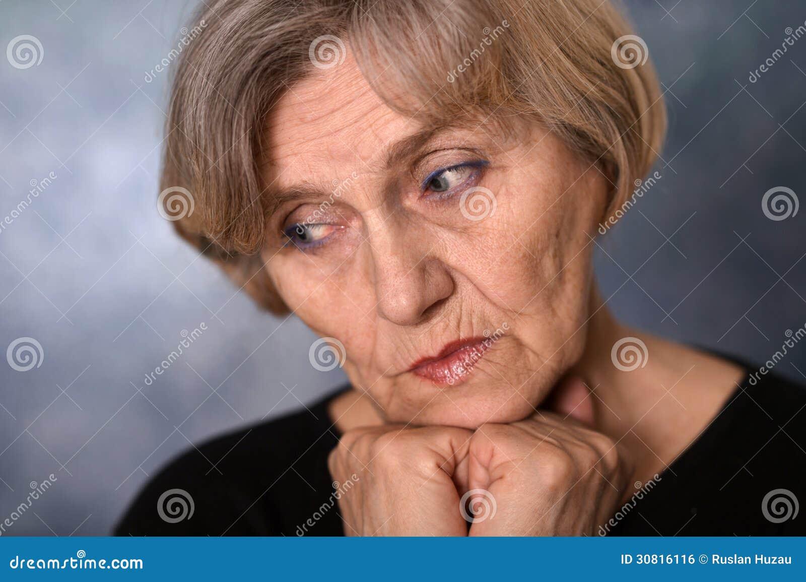 Retrato do close-up de uma mulher idosa de pensamento
